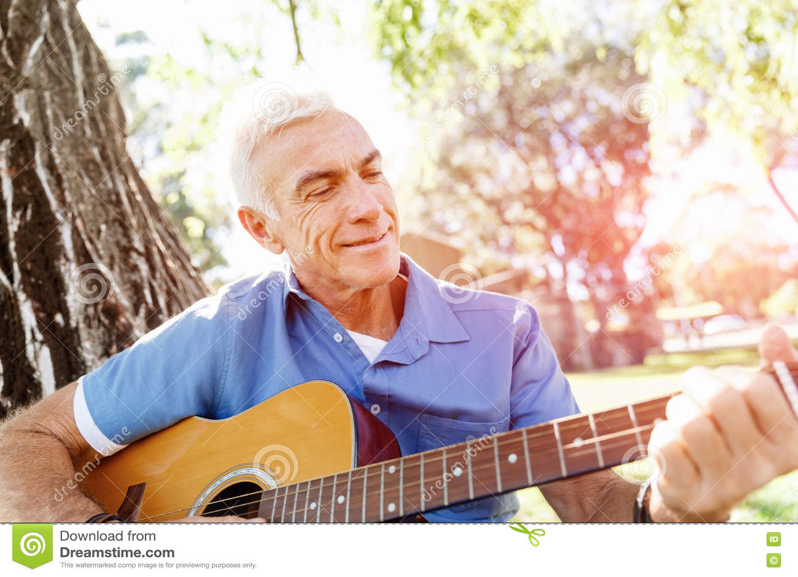 Hög man som utomhus plying gitarren
