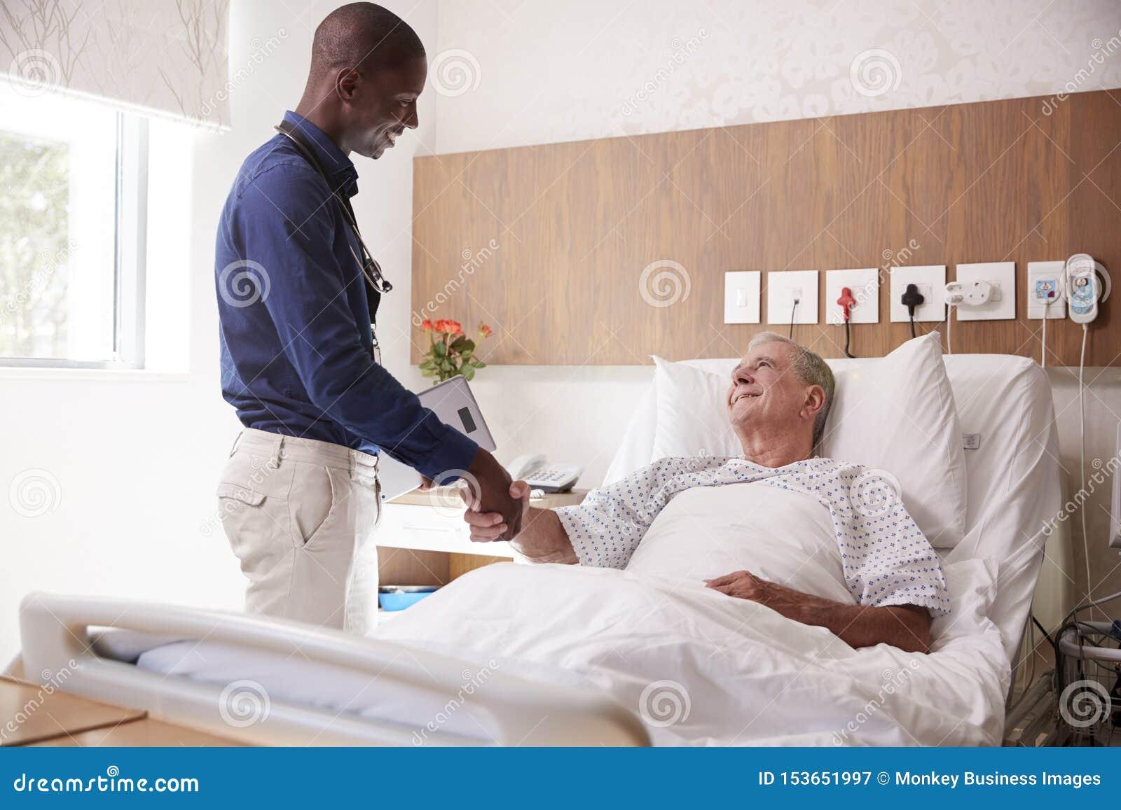 Hög manlig patient för doktor Shaking Hands With i sjukhussäng i geriatrisk enhet