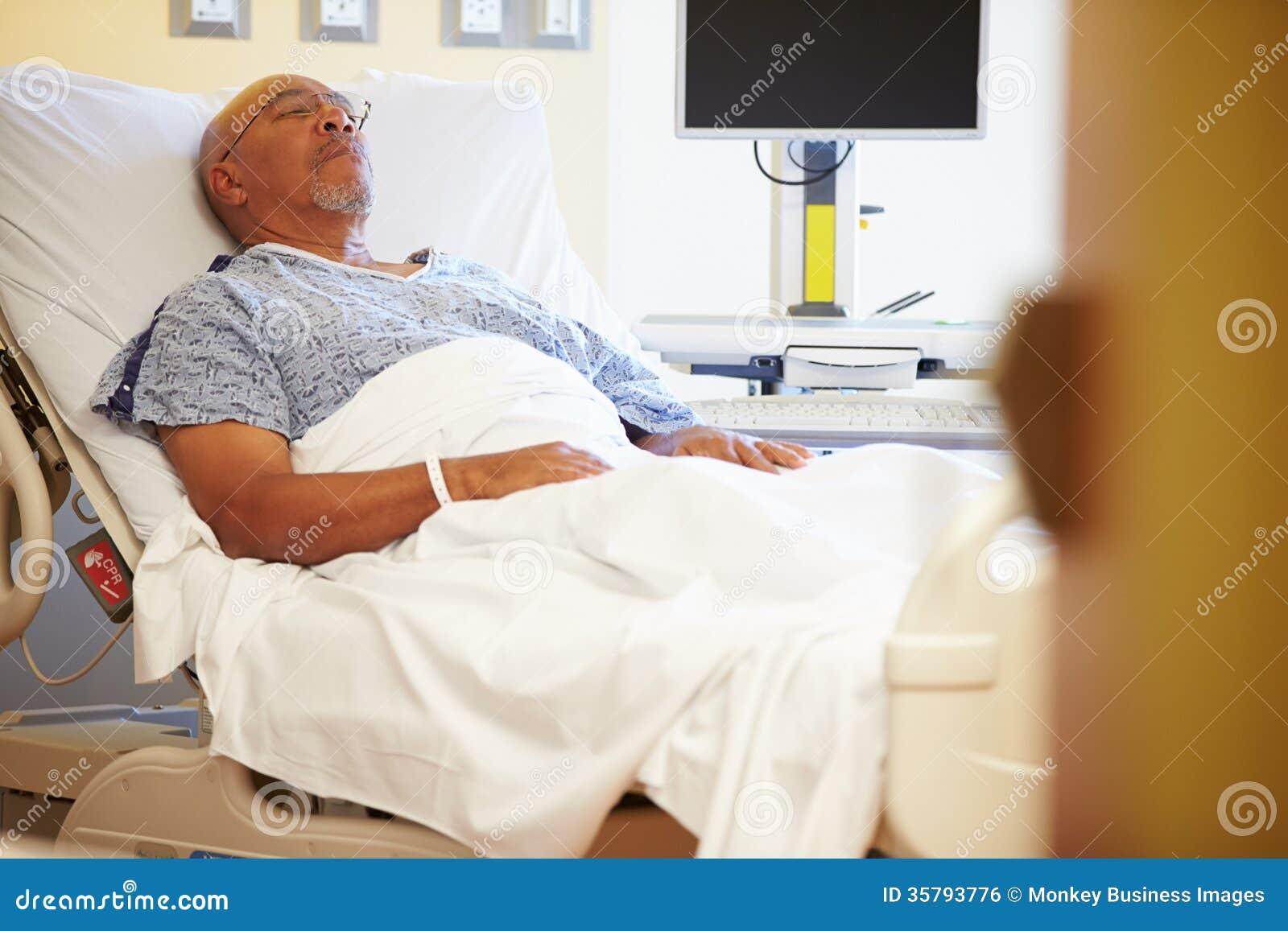 Hög manlig patient som vilar i sjukhussäng