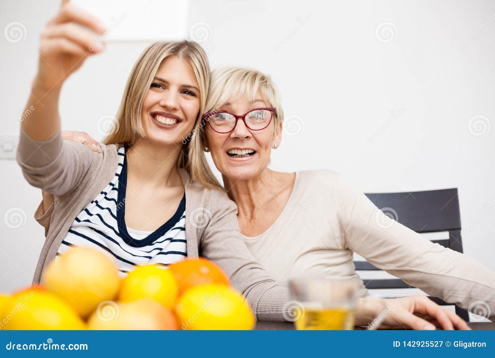 Hög moder och hennes dotter som ler och tar en selfie, medan sitta vid matställetabellen i ljust rum