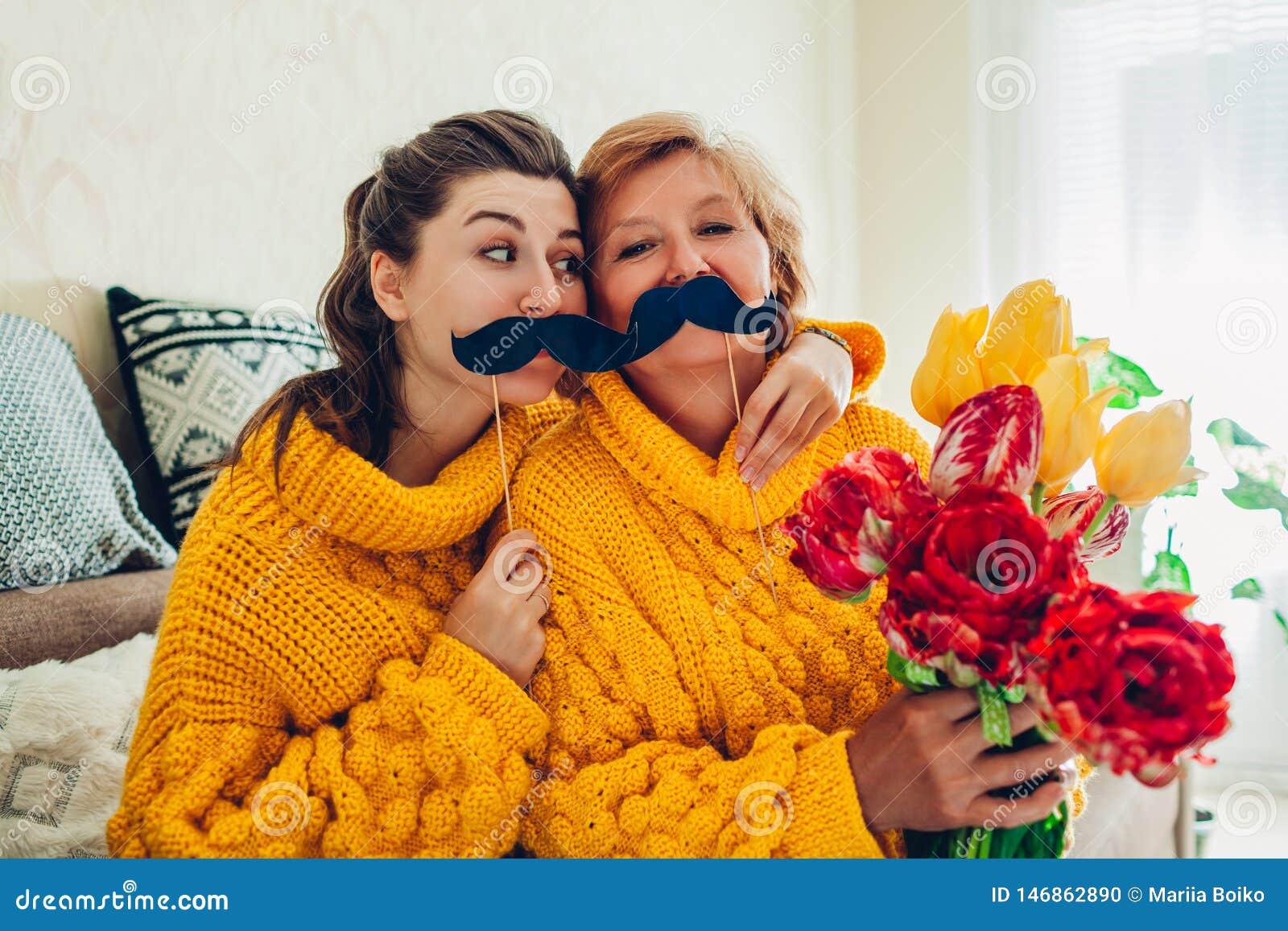 Hög moder och hennes vuxen dotter som tar selfie med blommor genom att använda fotobåsstöttor hemma Fostra dagbegreppet f?r ` s