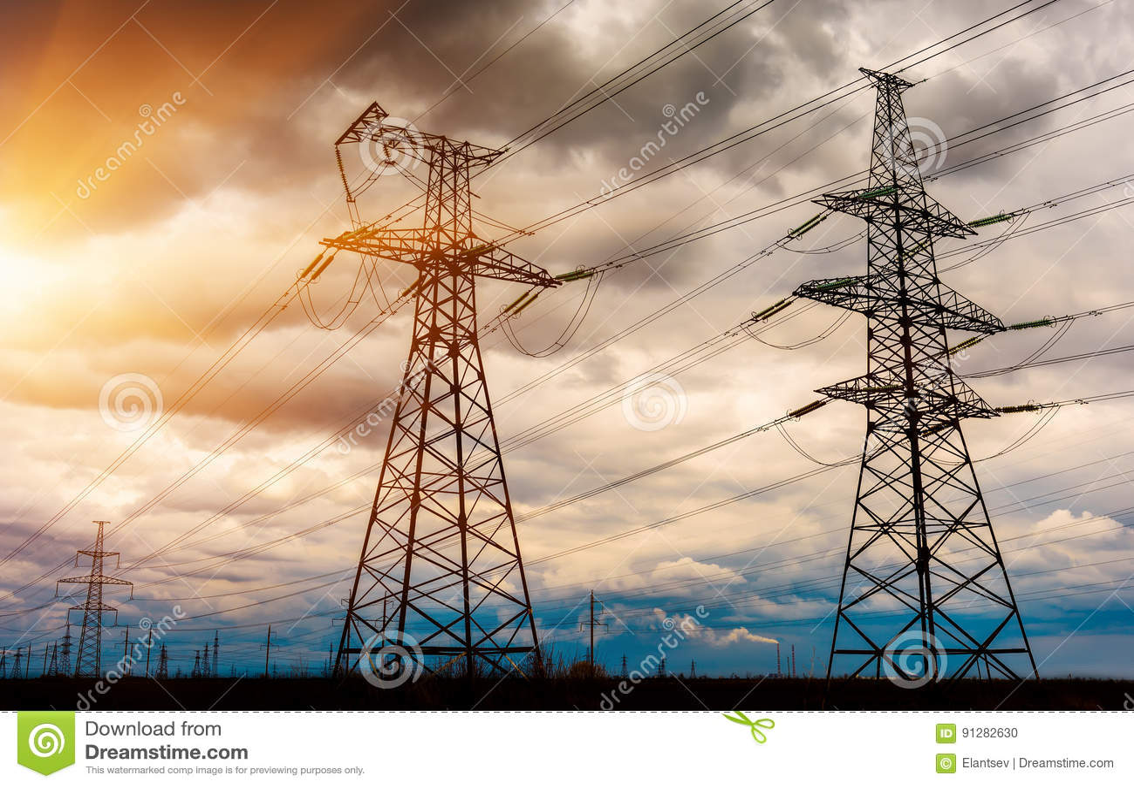 Hög-spänning kraftledningar på solnedgången Elektricitetsfördelningsstation