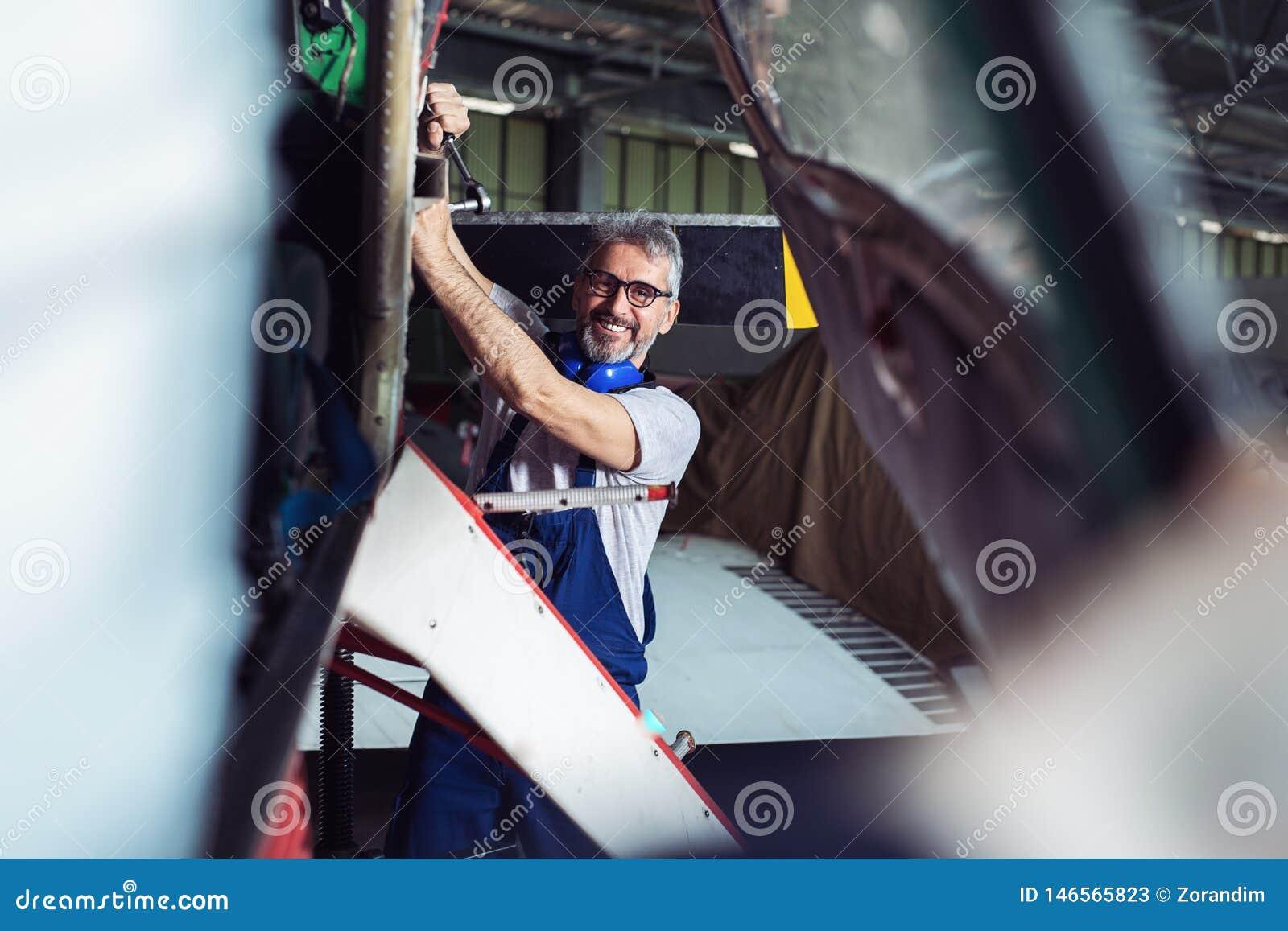 Hög tekniker som reparerar flygplanmotorn
