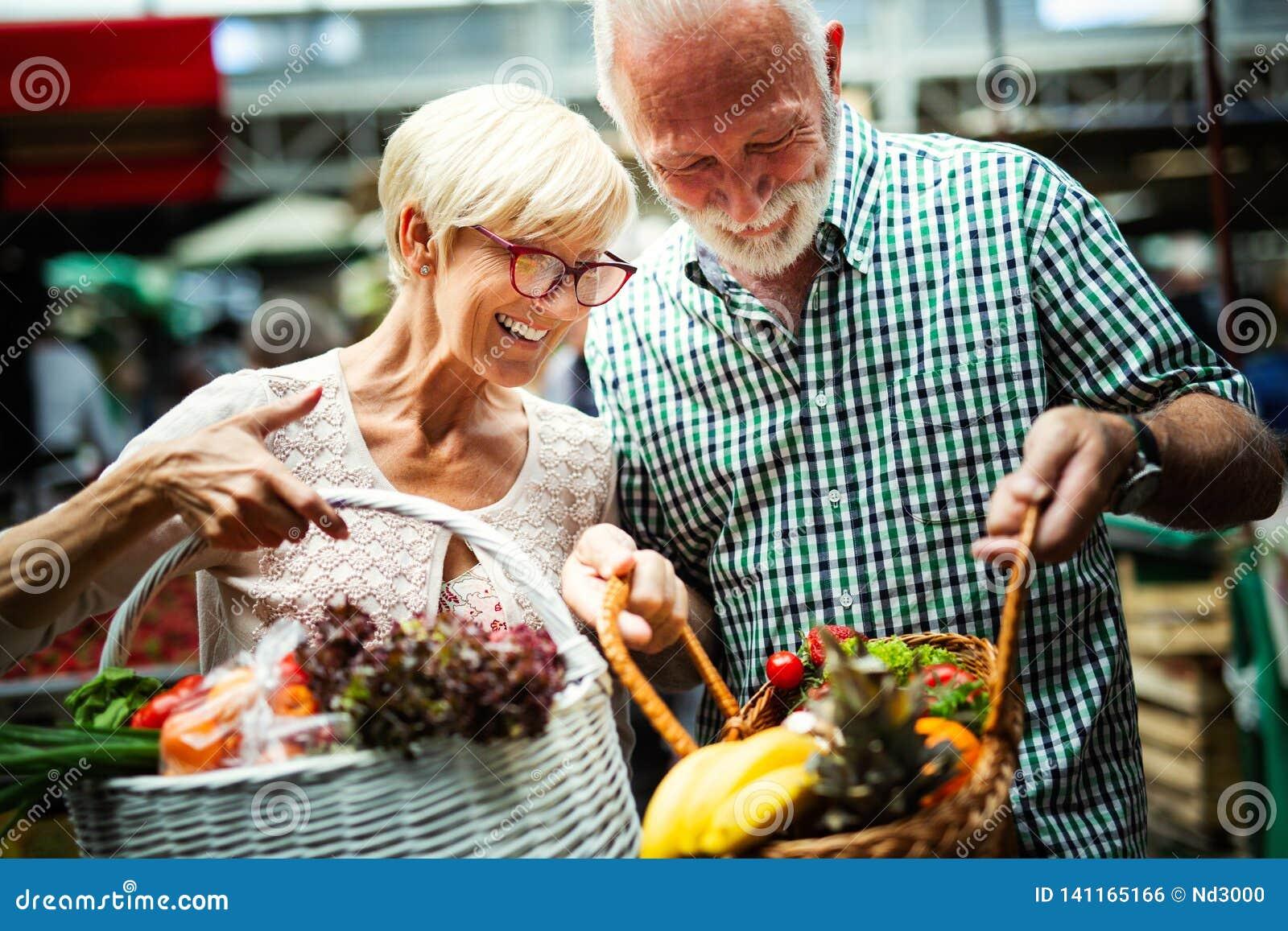 Höga familjpar som väljer den bio matfrukt och grönsaken på marknaden under veckoshopping
