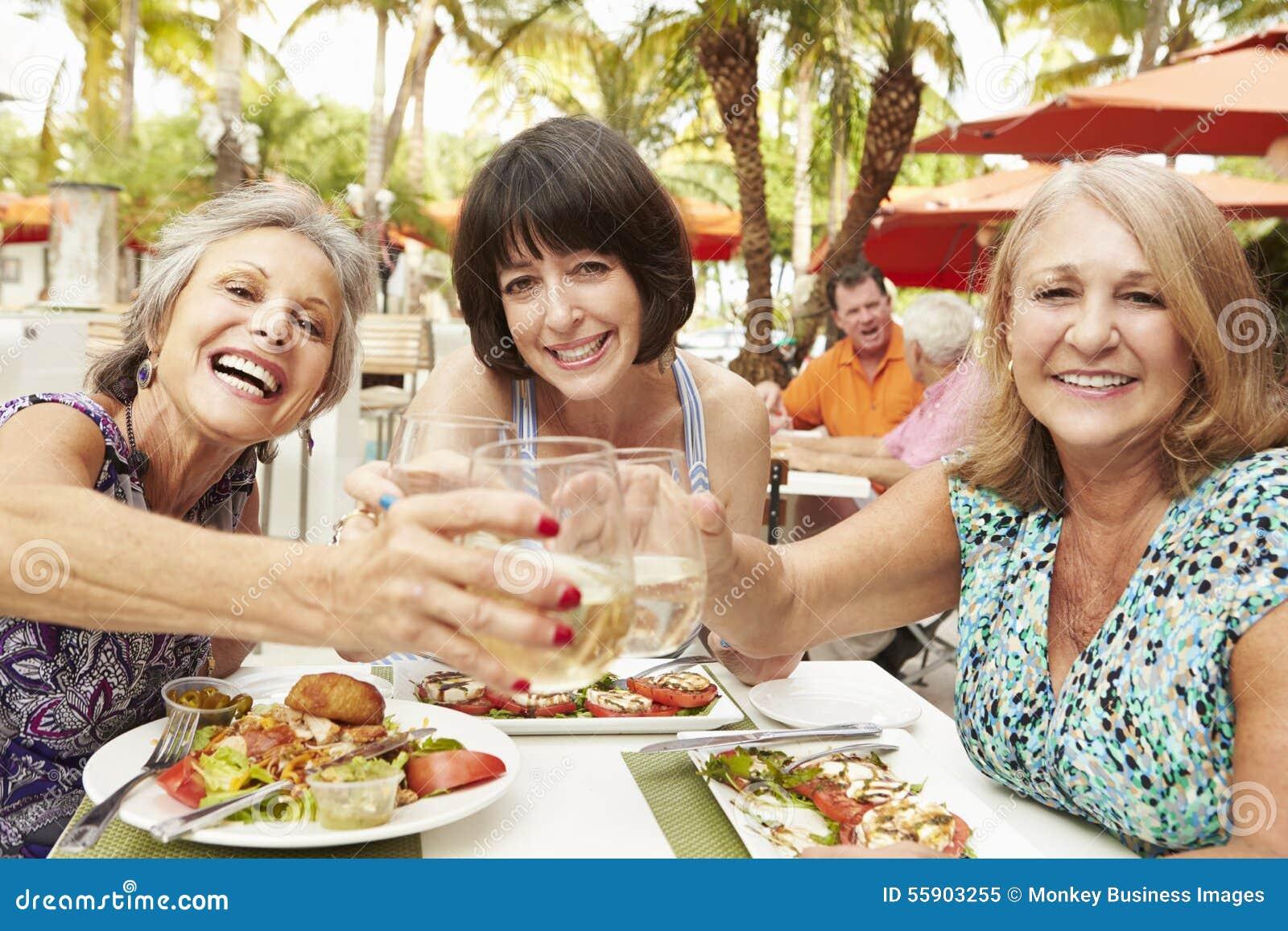 Höga kvinnliga vänner som äter mål i utomhus- restaurang