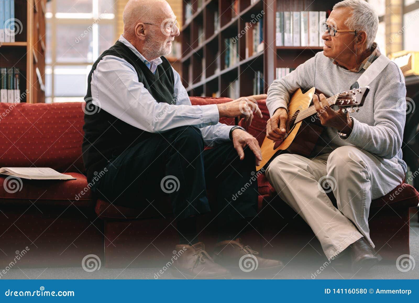 Höga män som spelar gitarren