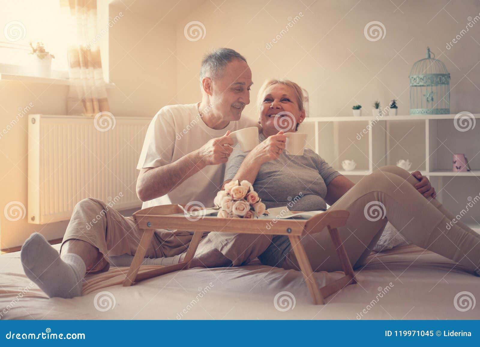 Höga par i underlag Högt folk som dricker kaffe i säng