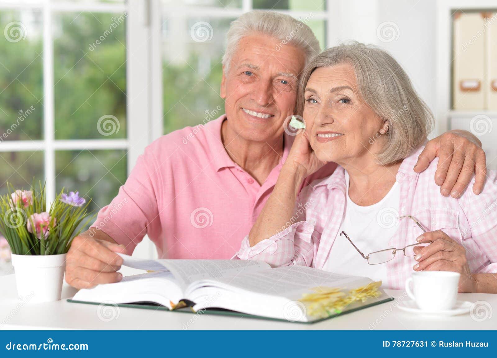 Höga par med boken som dricker te