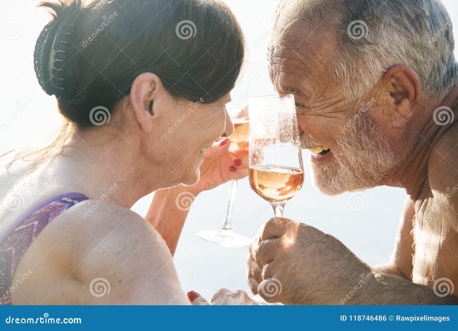 Höga par som dricker prosecco i en simbassäng