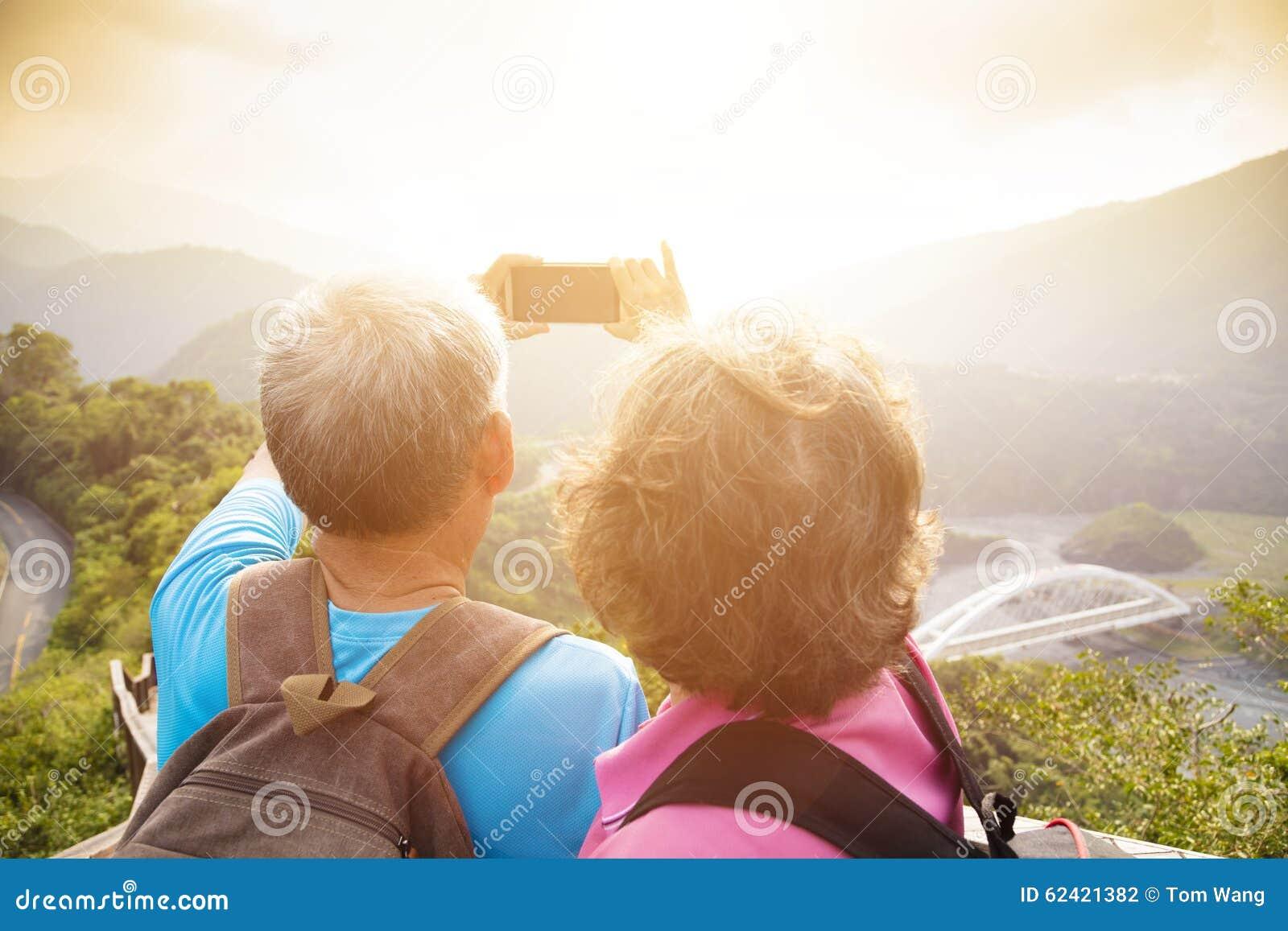 Höga par som fotvandrar på berg och tar selfies
