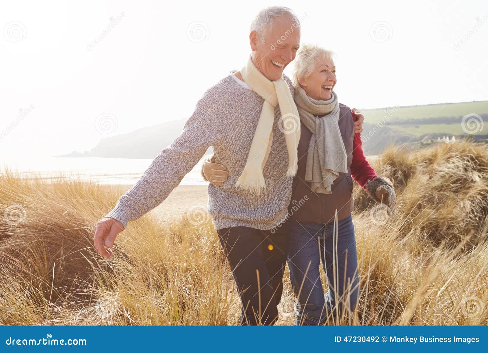 Höga par som går till och med sanddyn på vinterstranden