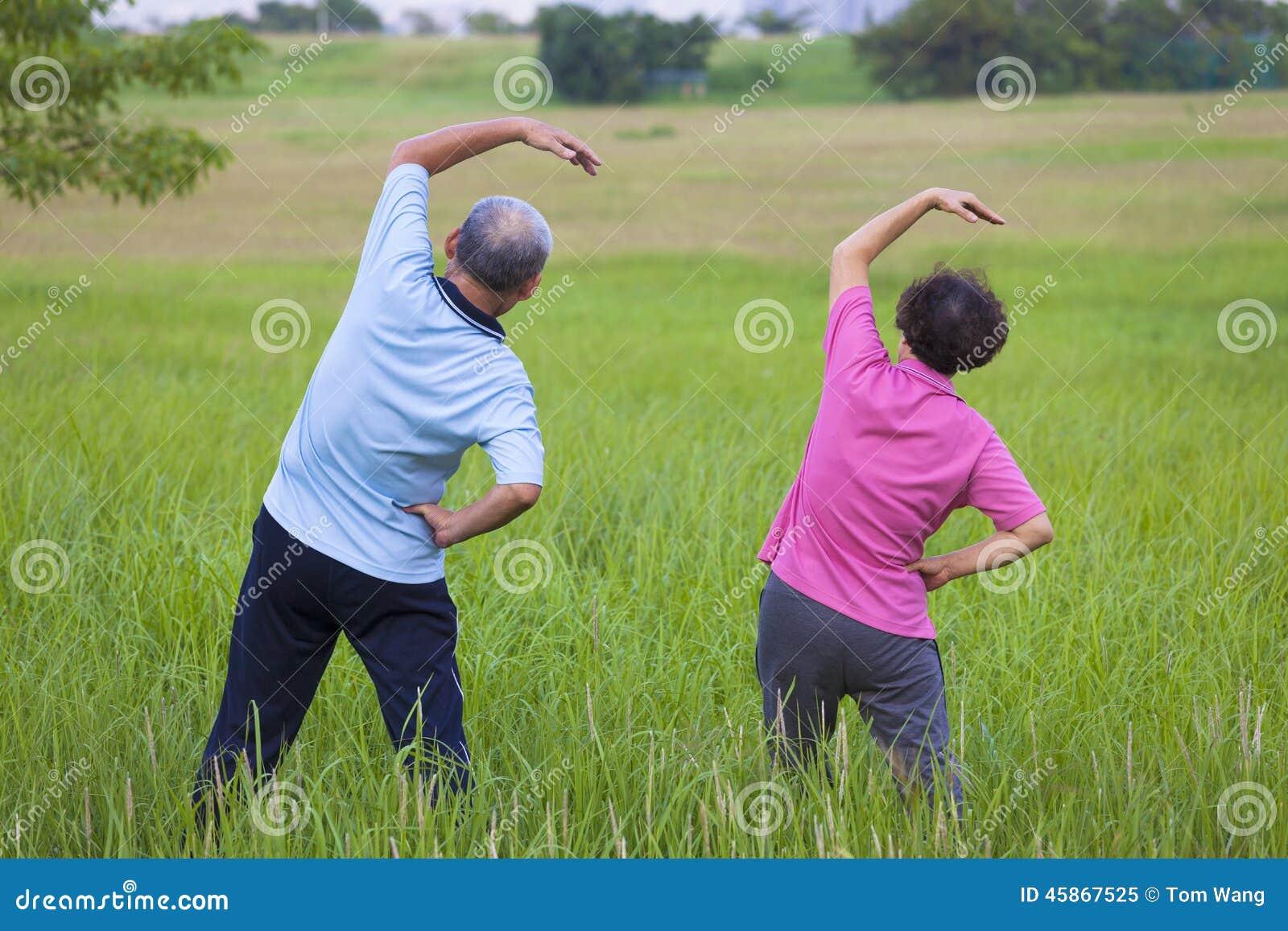 Höga par som gör gymnastik i parkera sunt begrepp