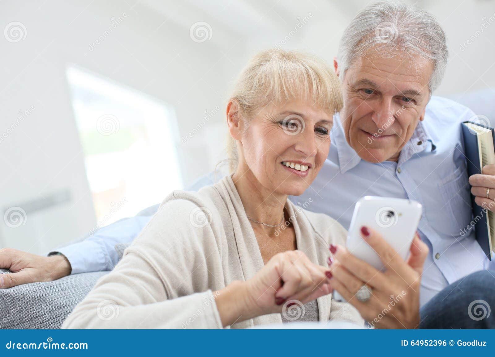 Höga par som har den roliga användande smartphonen