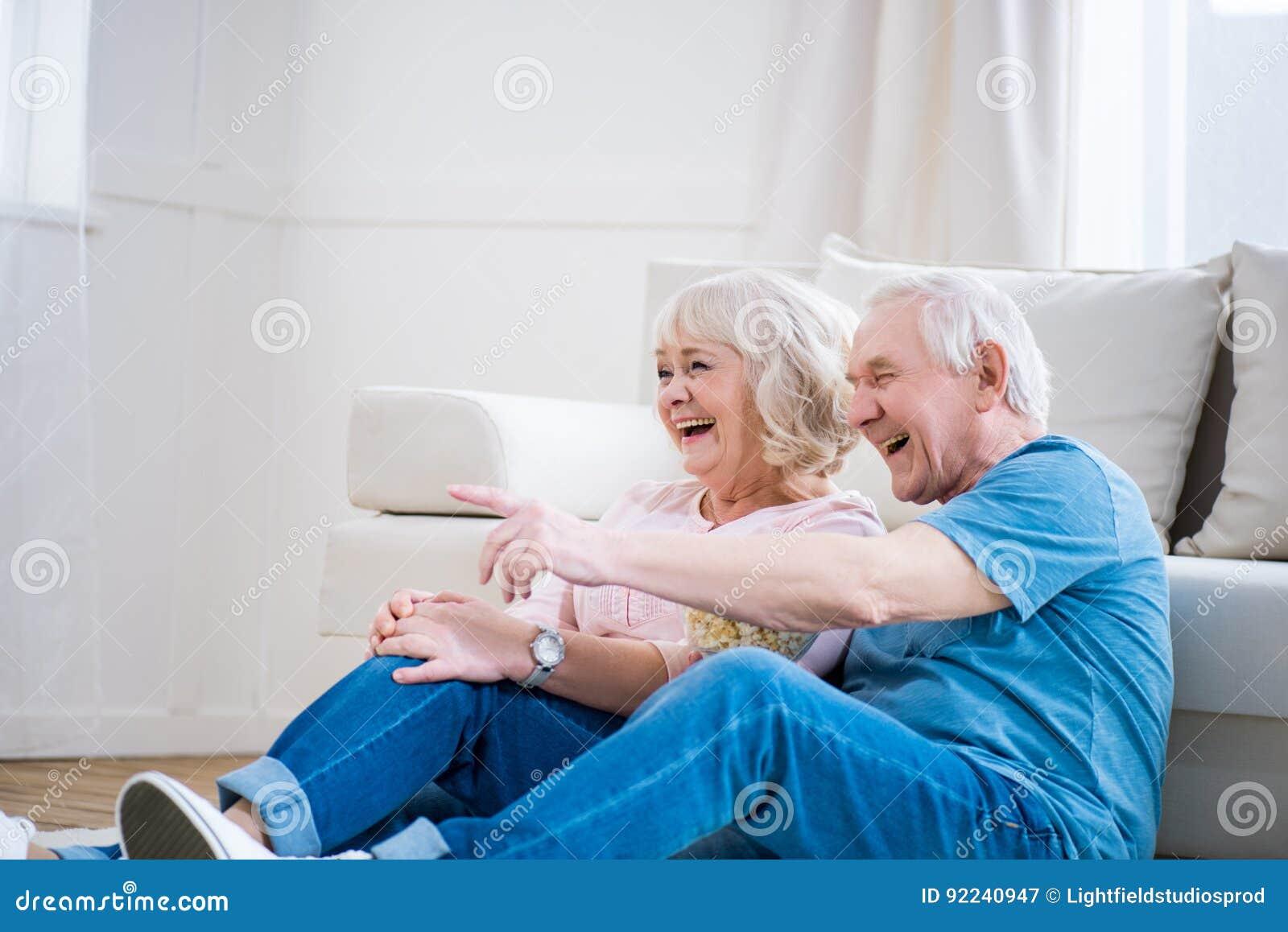 Höga par som skrattar och sitter på golvet, peka för man