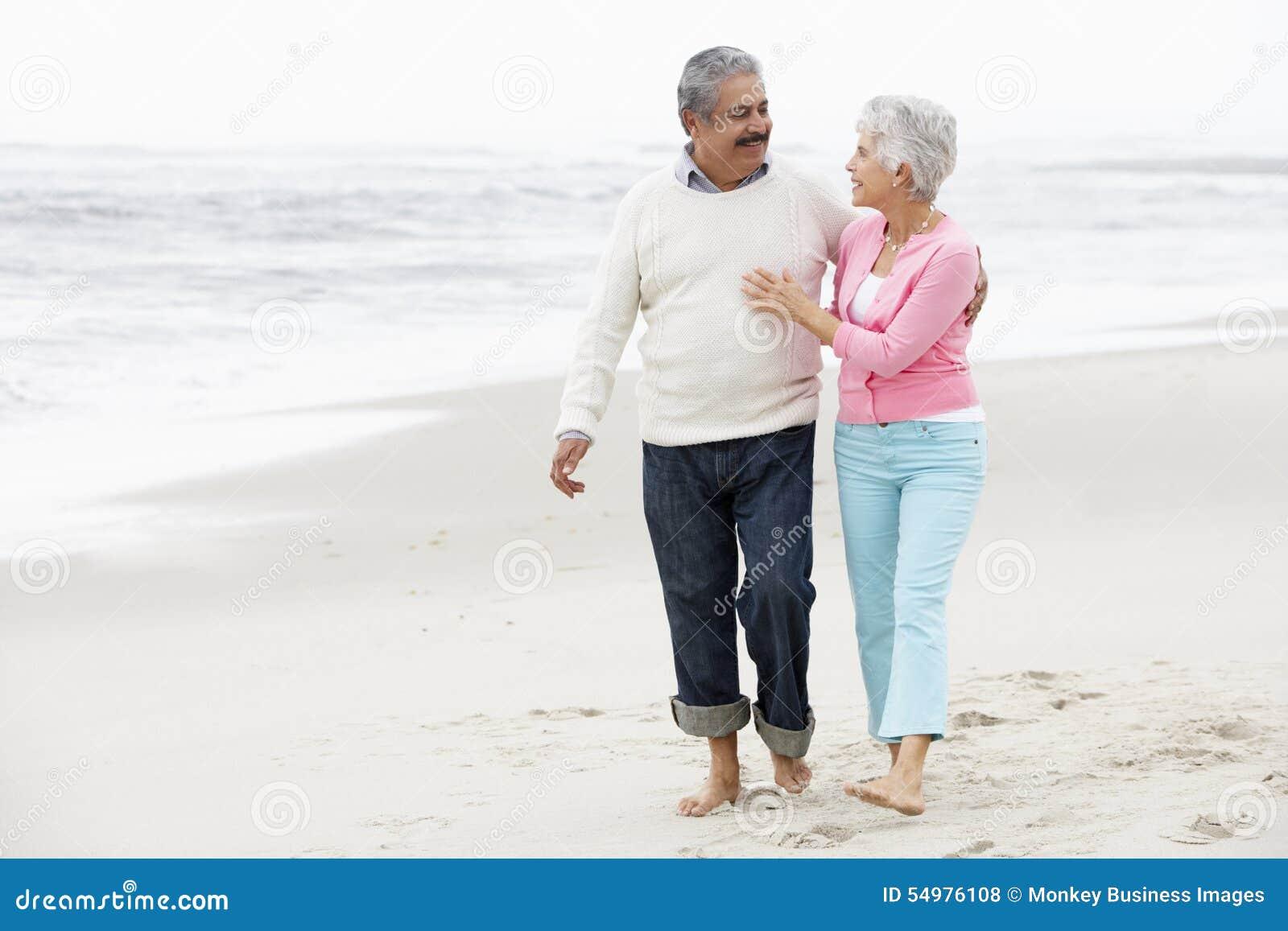 Höga par som tillsammans går längs strand