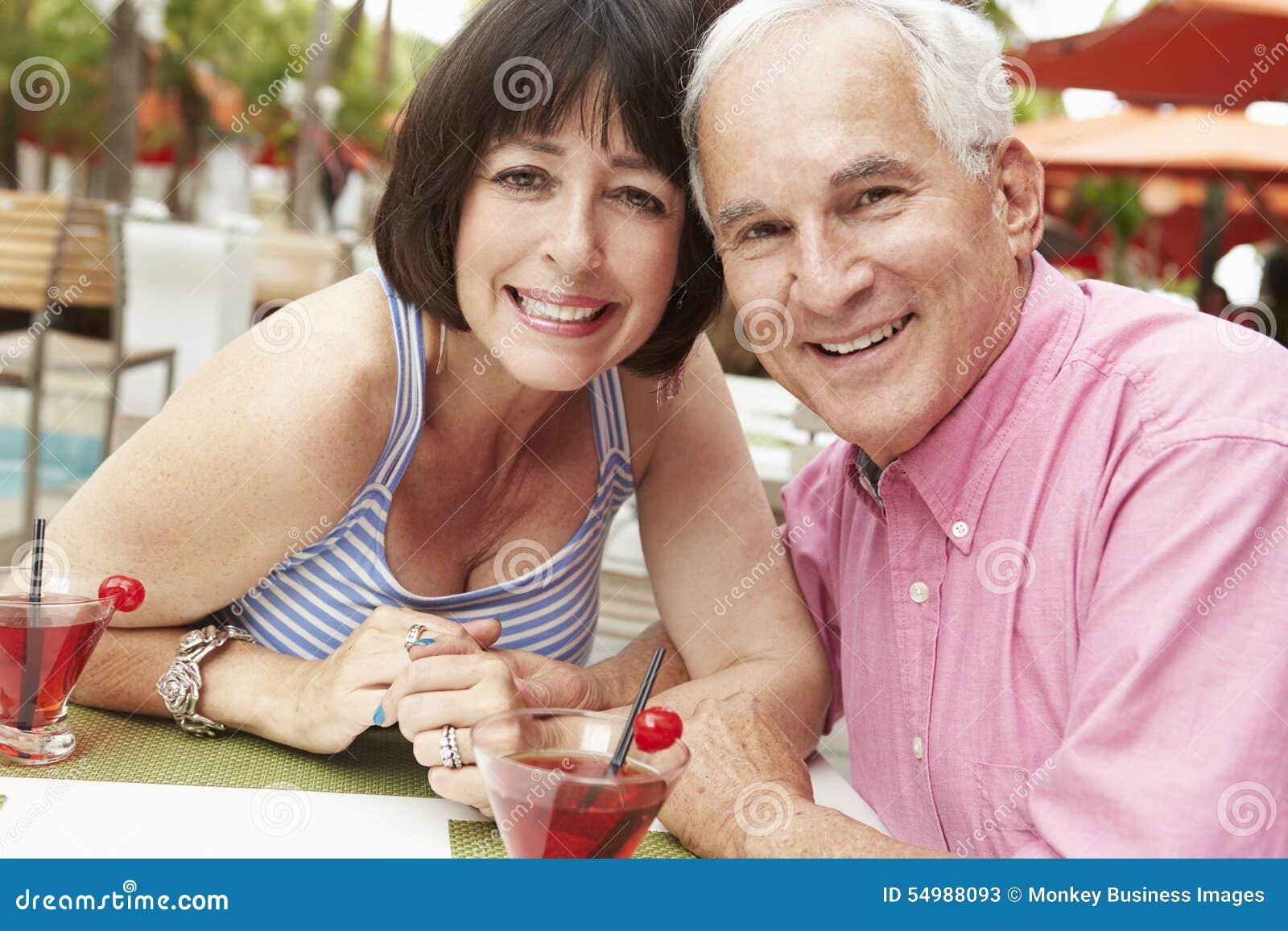 Höga par som tillsammans tycker om coctailar i utomhus- stång