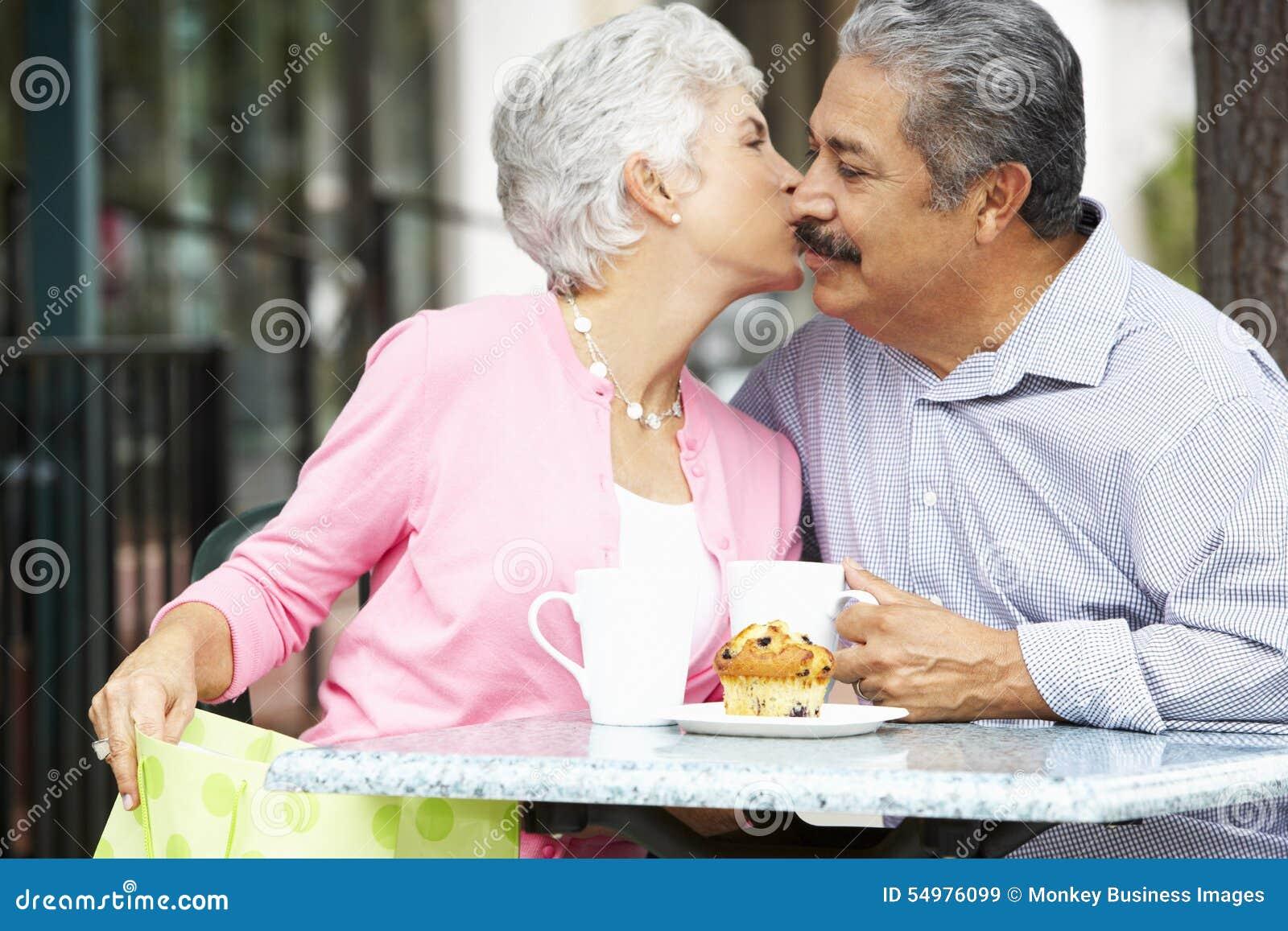 Höga par som tycker om mellanmålet på utomhus- CafÅ ½, når att ha shoppat