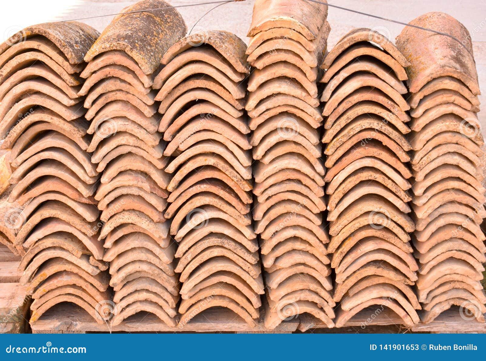 Högar av gamla taktegelplattor i många rader med olikt nummer i någon kolonn De forntida tegelplattorna befläckas med damm och la
