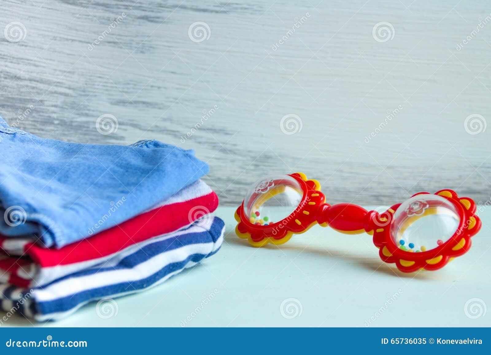 Högen av behandla som ett barn kläder I på tabellträbakgrund