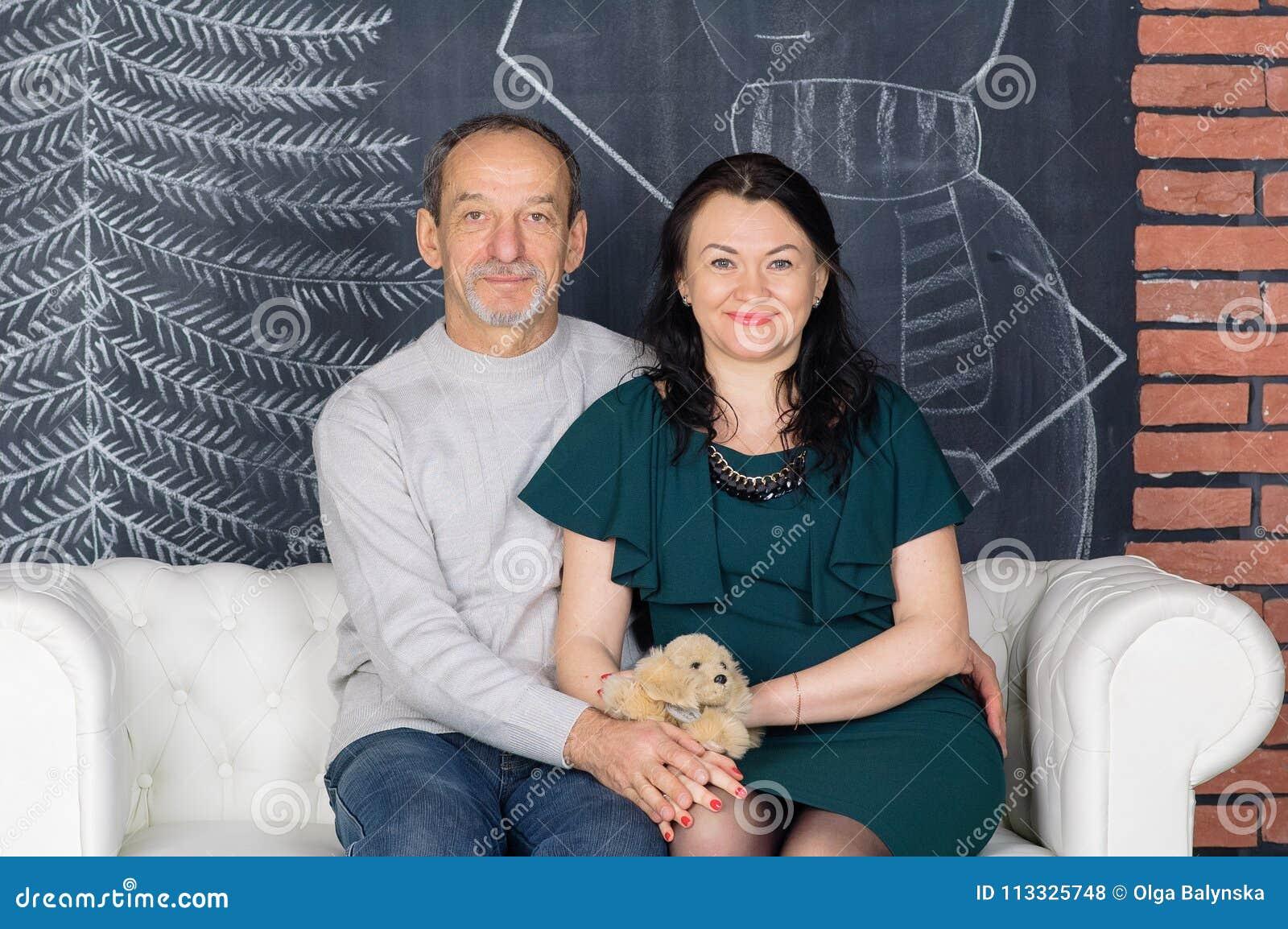 Högt Grå färg-haired mansammanträde på den vita Sofa Hugging His medelåldersa frun i mörker - grön klänning Lyckliga par med ålde