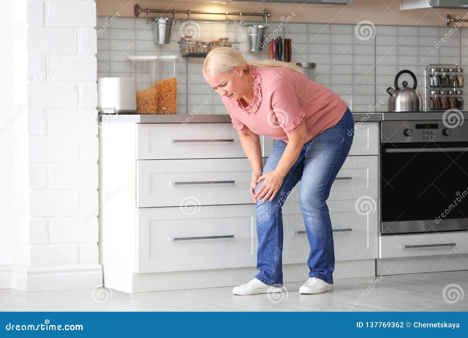 Högt kvinnalidande från knä smärtar i kök