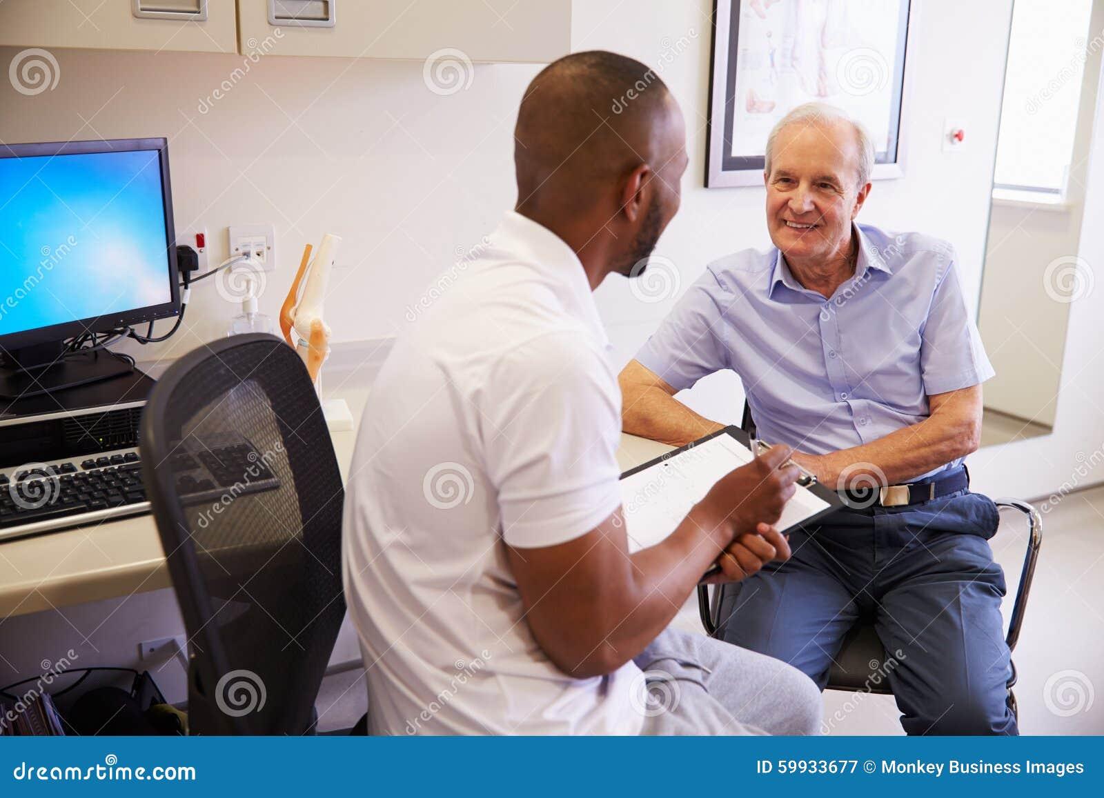 Högt manligt tålmodigt arbete med fysioterapeuten In Hospital