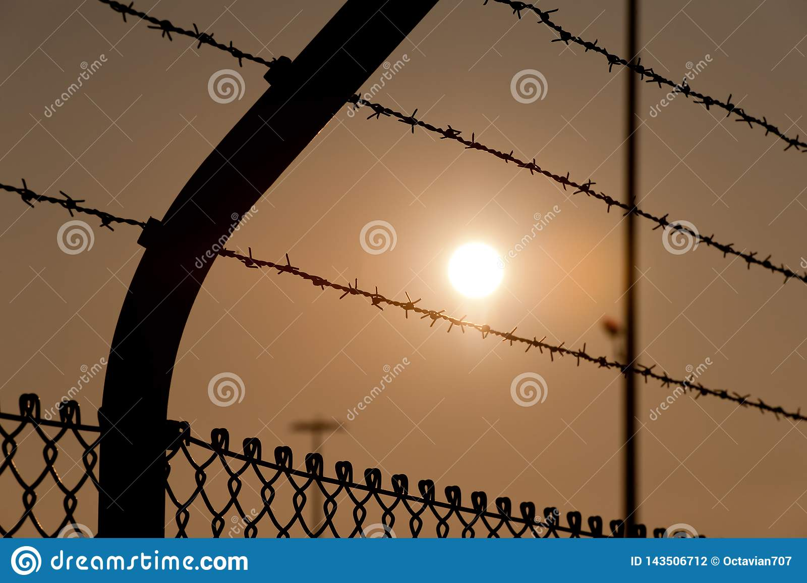 Högt staket med taggtråd i solnedgång