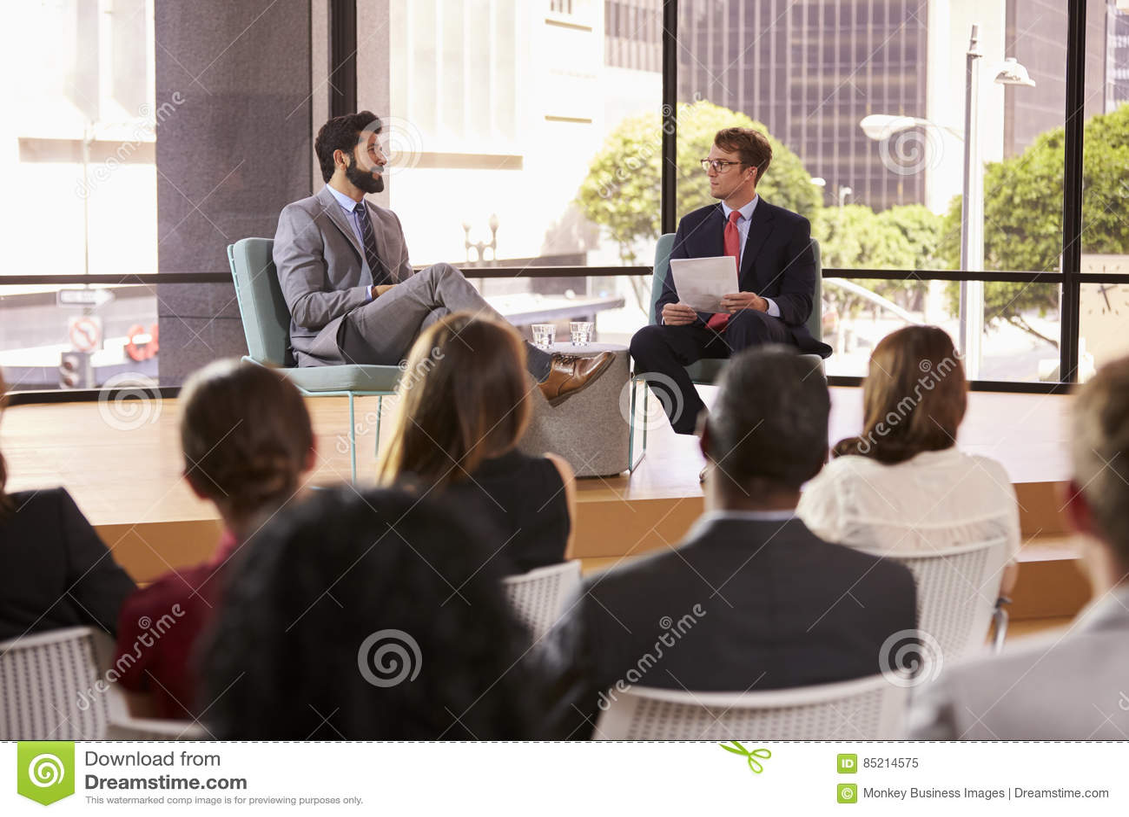 Högtalare och intervjuare framme av åhörare på ett seminarium
