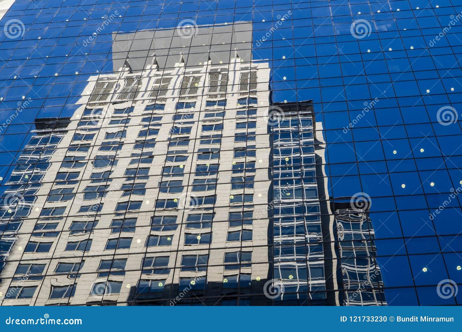 Högväxt byggnad reflekterar på klart blått glass fönster av högväxt byggnad