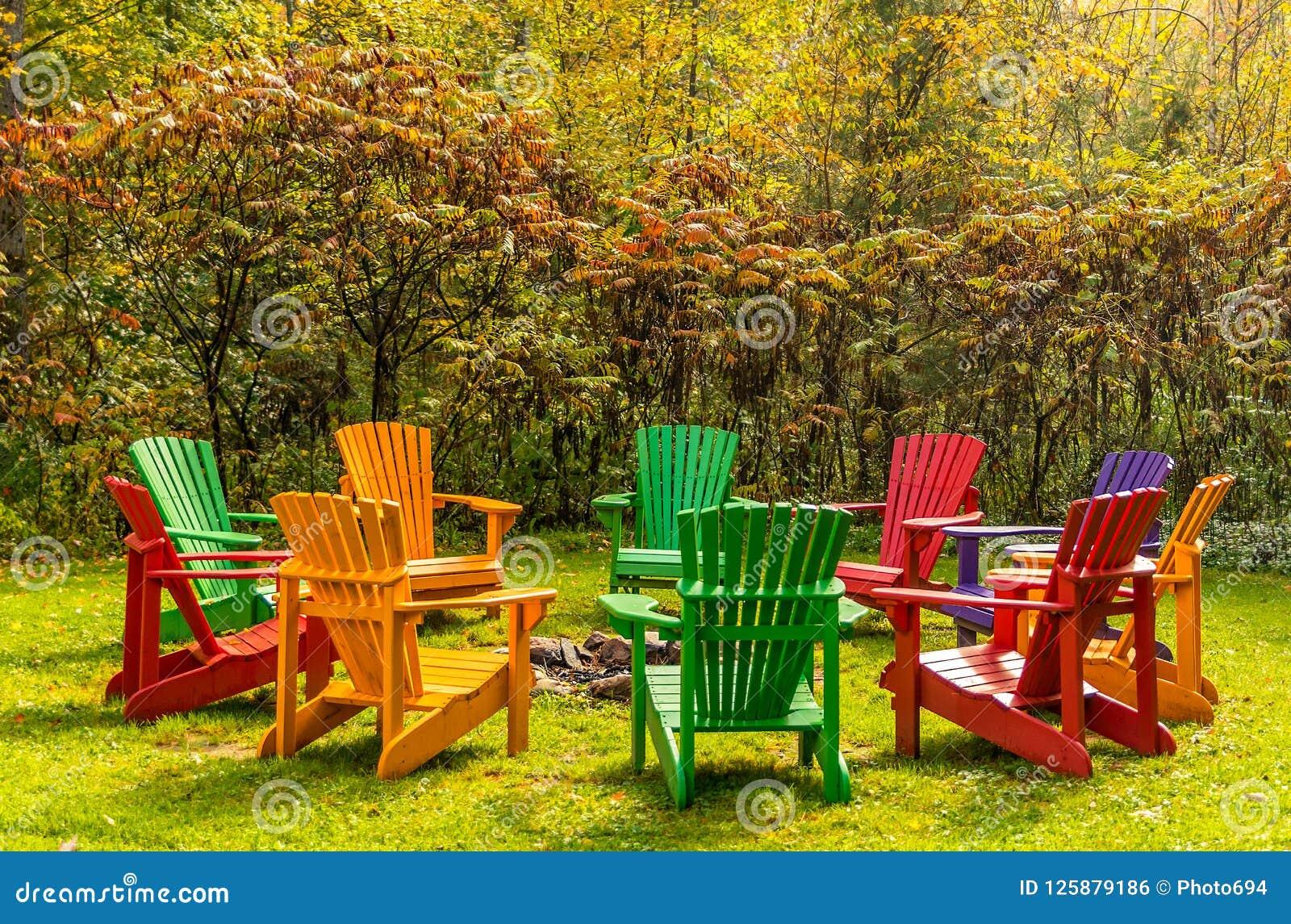 Hölzerne adirondack Stühle vereinbarten in einem Kreis um eine Feuergrube