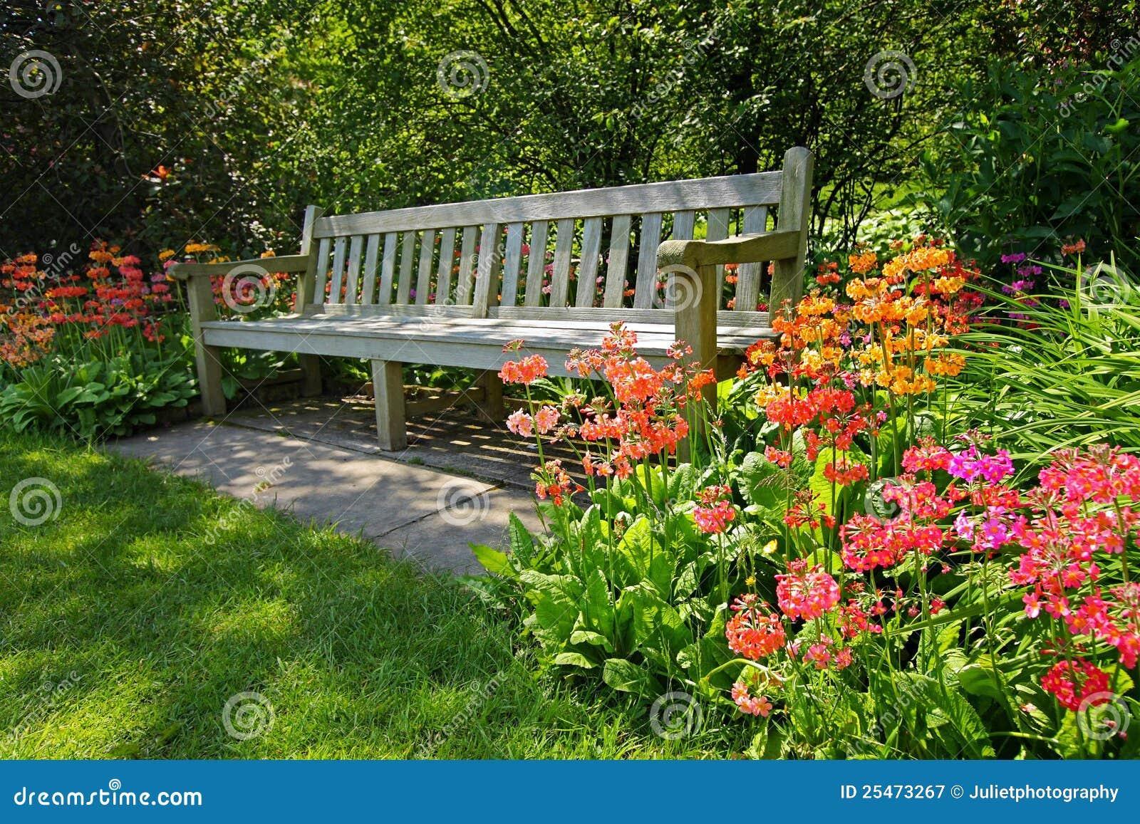 Hölzerne Bank und helle blühende Blumen