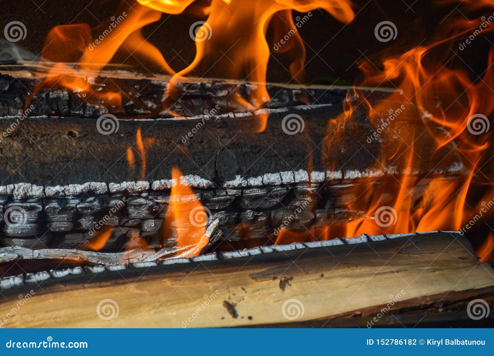 Hölzerne brennende heiße verkohlte Planken des Holzes meldet ein Feuer mit den Zungen des Feuers und des Rauches an Beschaffenhei