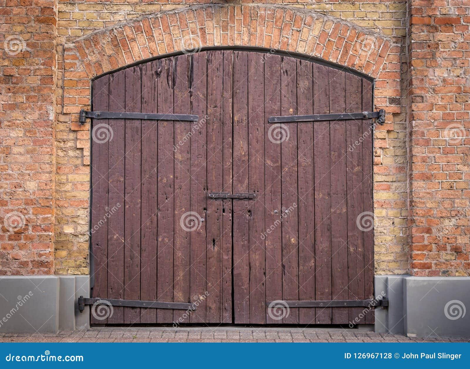 Hölzerne Doppeltüren Browns mit einem Bogen des roten Backsteins