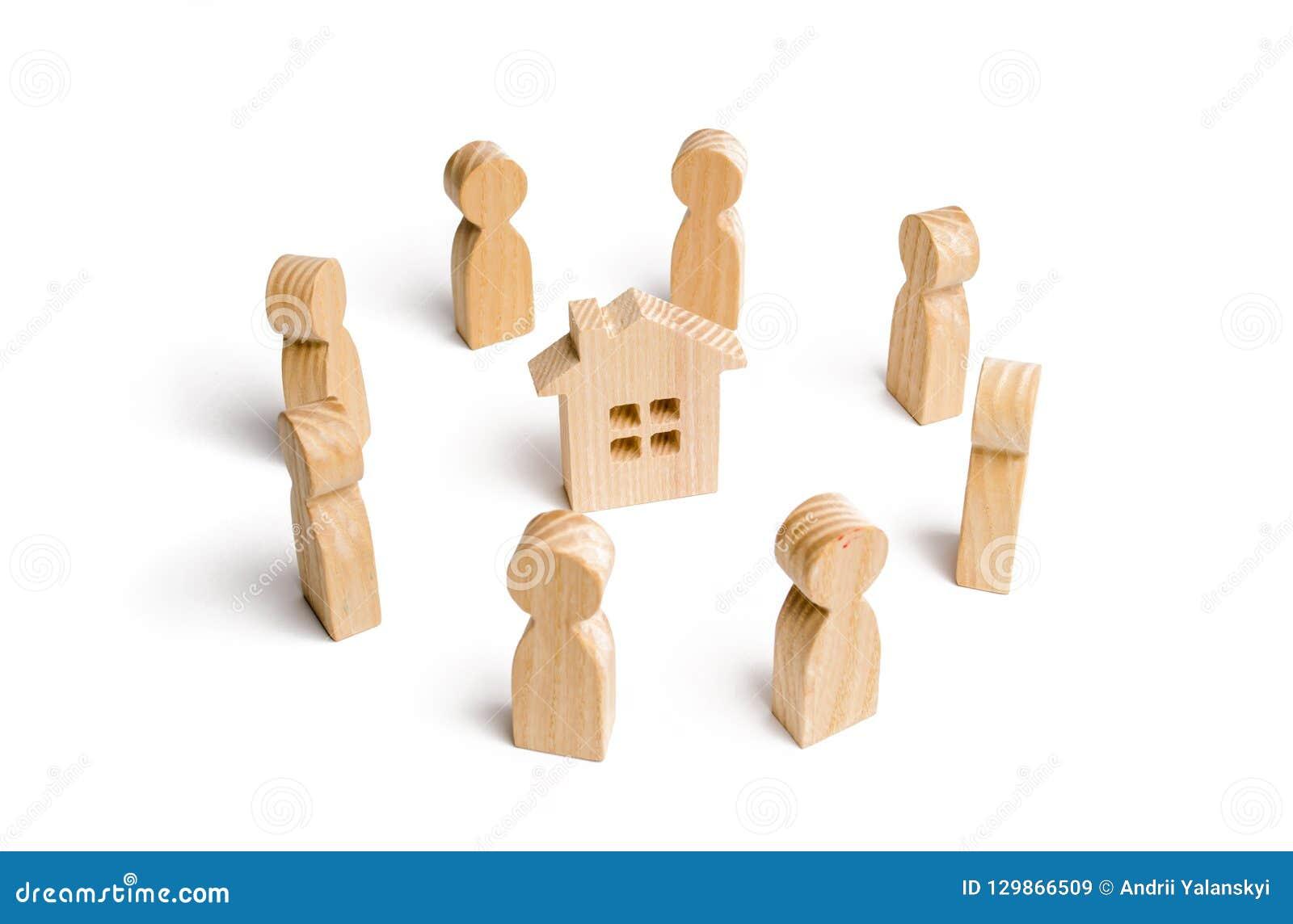 Hölzerne Figürchen des Leutestands um das Haus Suche nach einem neuen Haus und Immobilien Ein Haus kaufen oder verkaufend