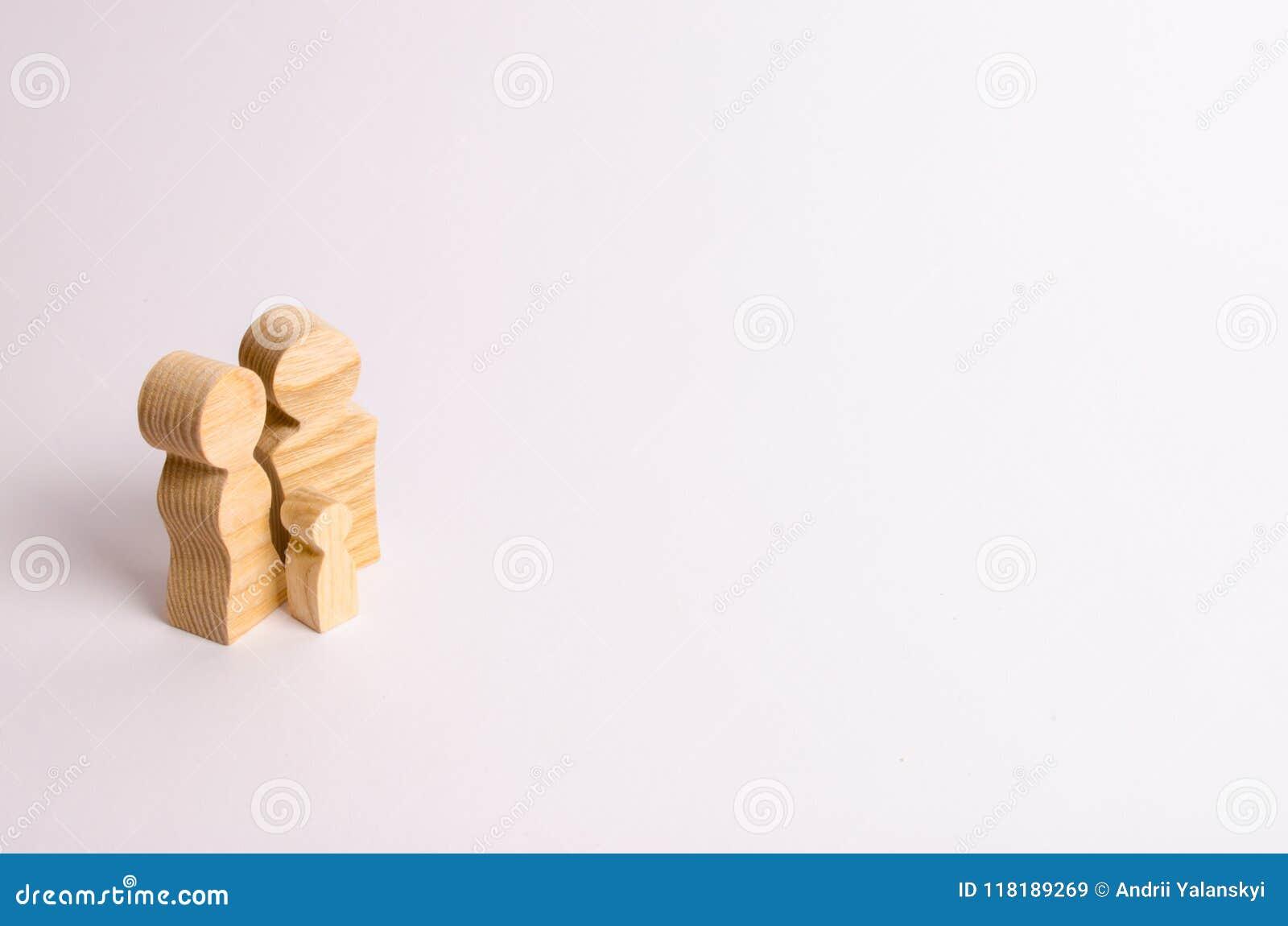 Hölzerne Figürchen von Eltern und von Kind auf einem weißen Hintergrund Minimalismus das Konzept der Familie und die Erziehung vo