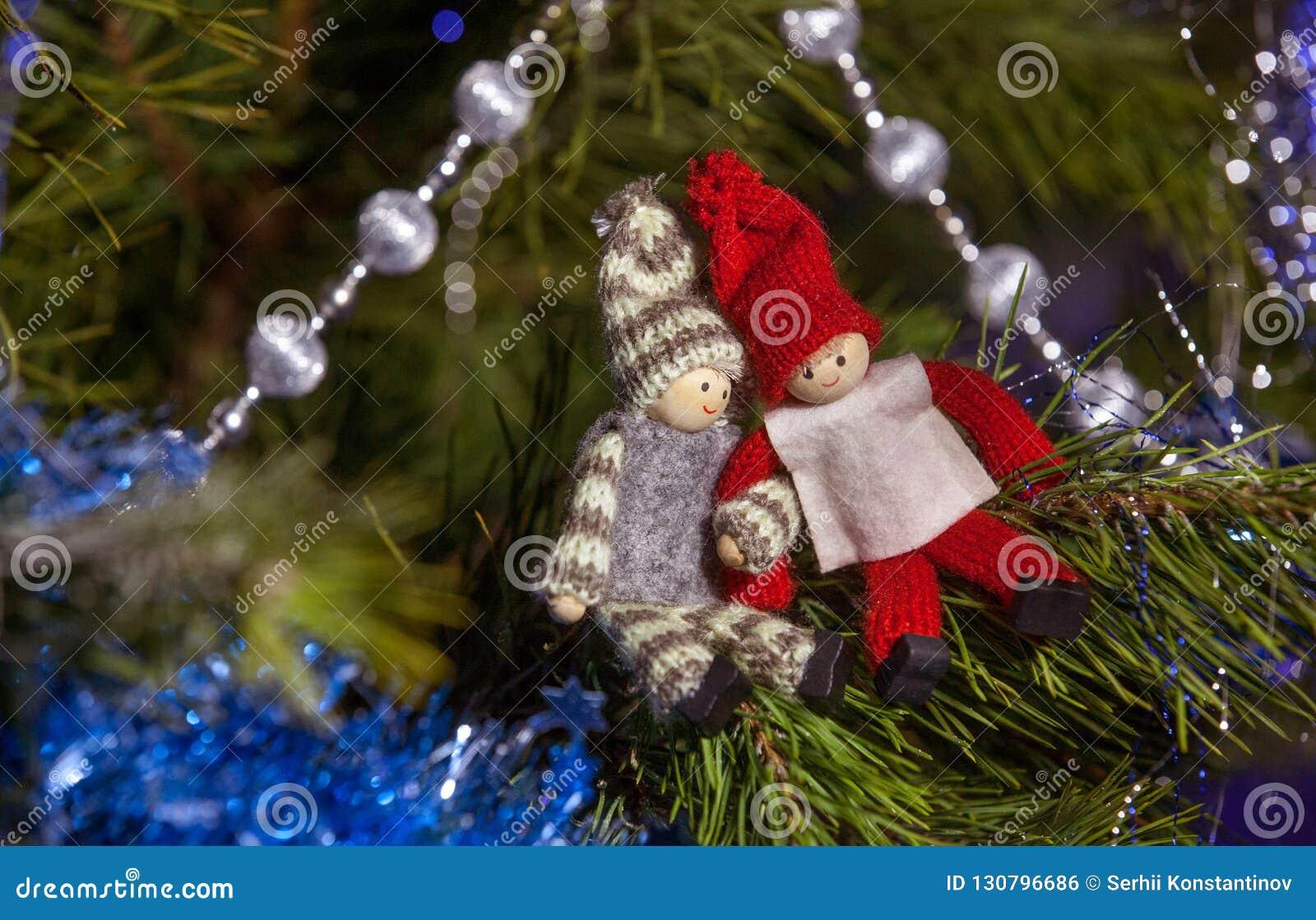 Hölzerne Jungen- und Mädchenfigürchen auf dem Weihnachtsbaumast Chri
