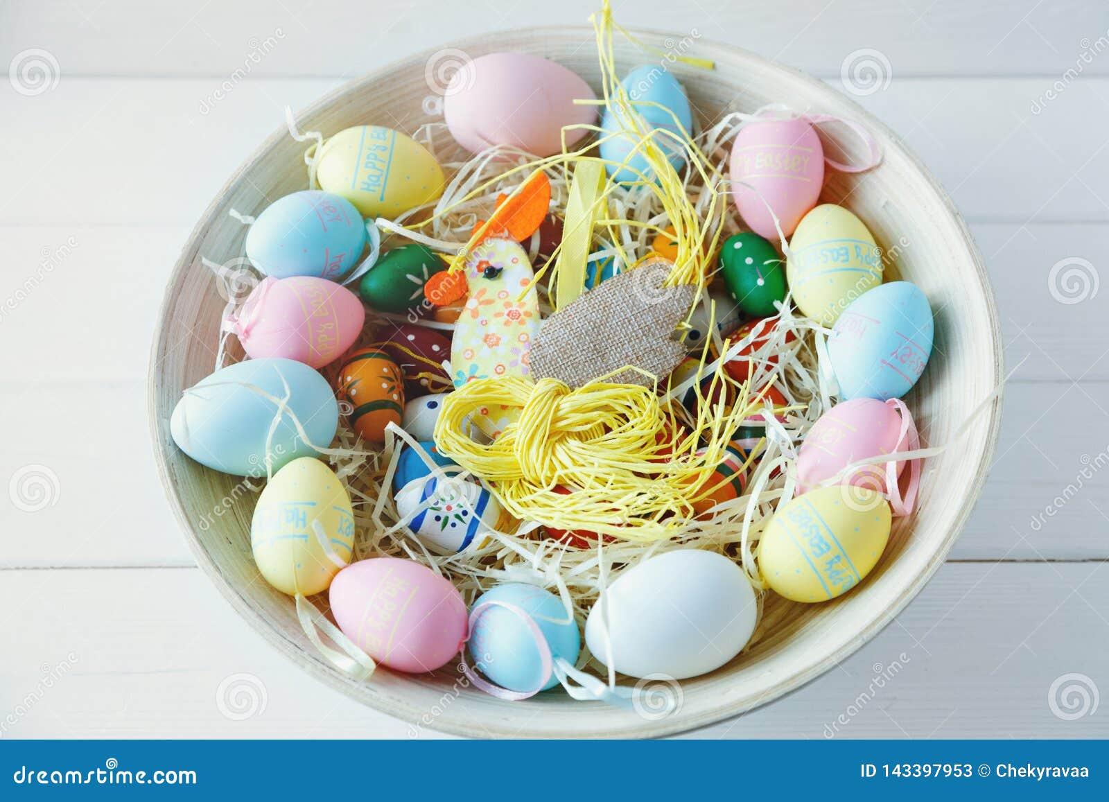 Hölzerne Schüssel mit Orange, gelb, Rosa und grünen Eiern auf weißem hölzernem Hintergrund Fröhliche Ostern! Dekoration
