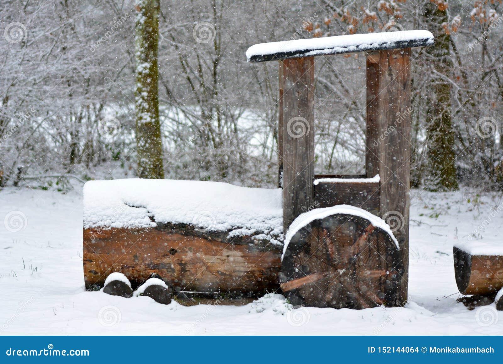 Hölzerne sich fortbewegende Bahnmaschine der großen Größe als Teil eines Spielplatzes bedeckt im Schnee während des Wintersturms