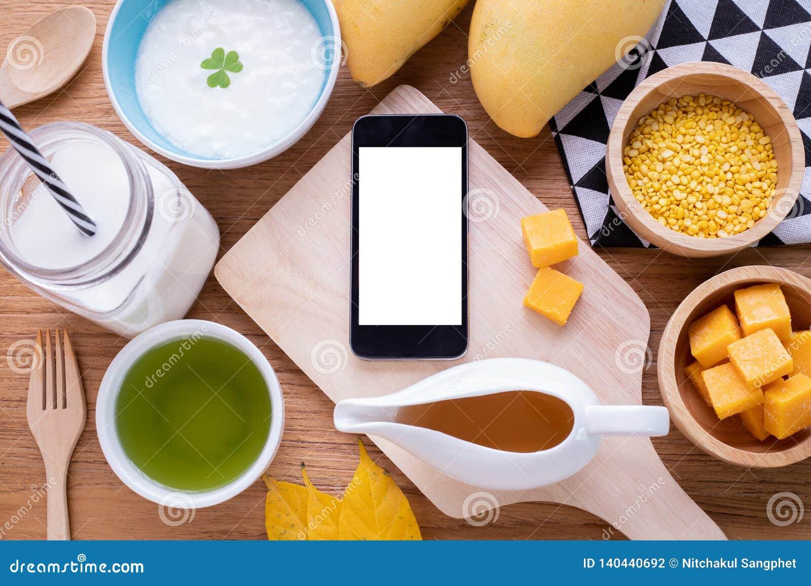 Hölzerne Tabelle mit leerem Bildschirm am intelligenten Telefon, Tablette, Handy mit Frühstück, Kopienraum