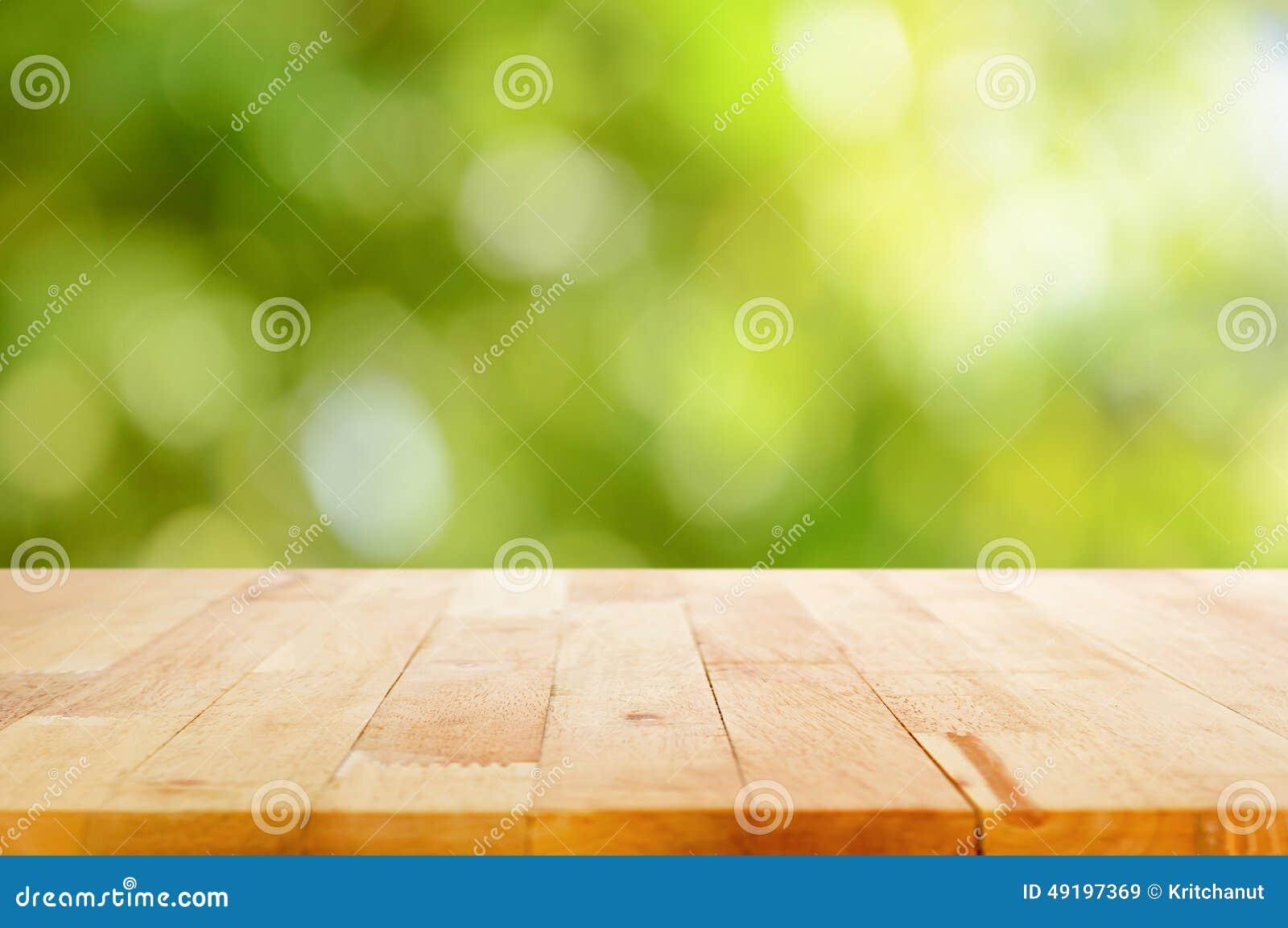 Hölzerne Tischplatte auf bokeh Zusammenfassungs-Grünhintergrund