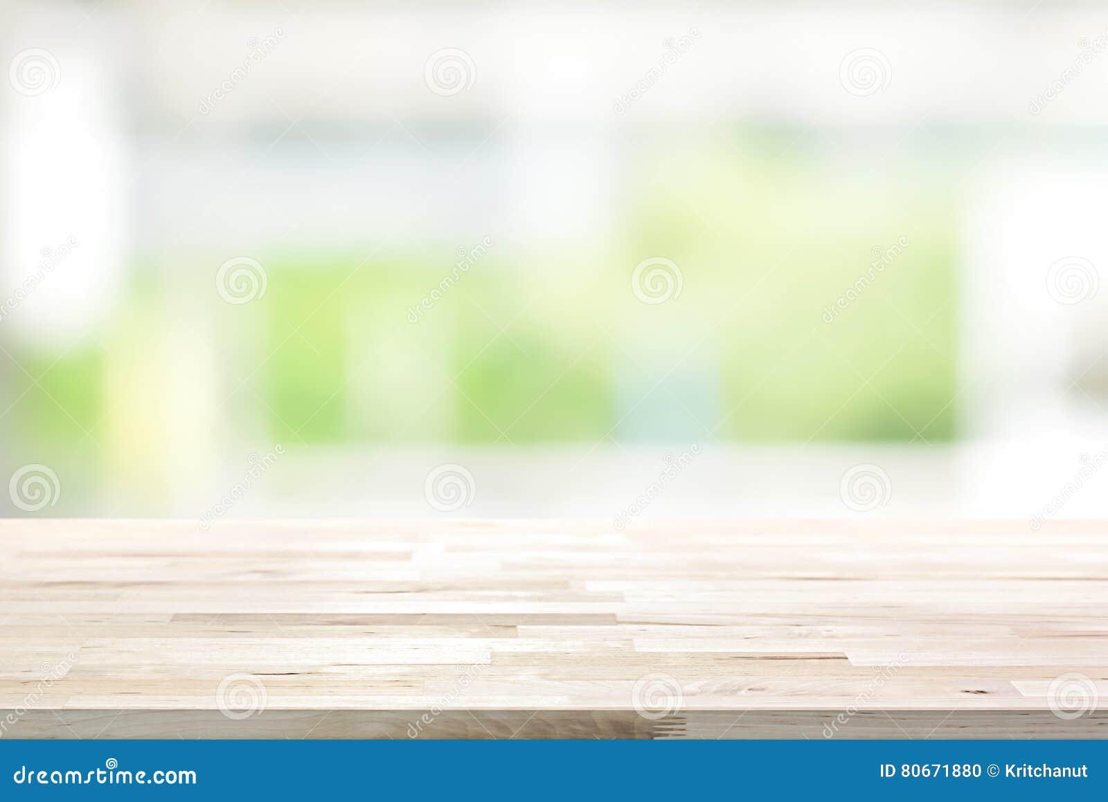 Hölzerne Tischplatte auf Küchen-Fensterhintergrund der Unschärfe weißem grünem