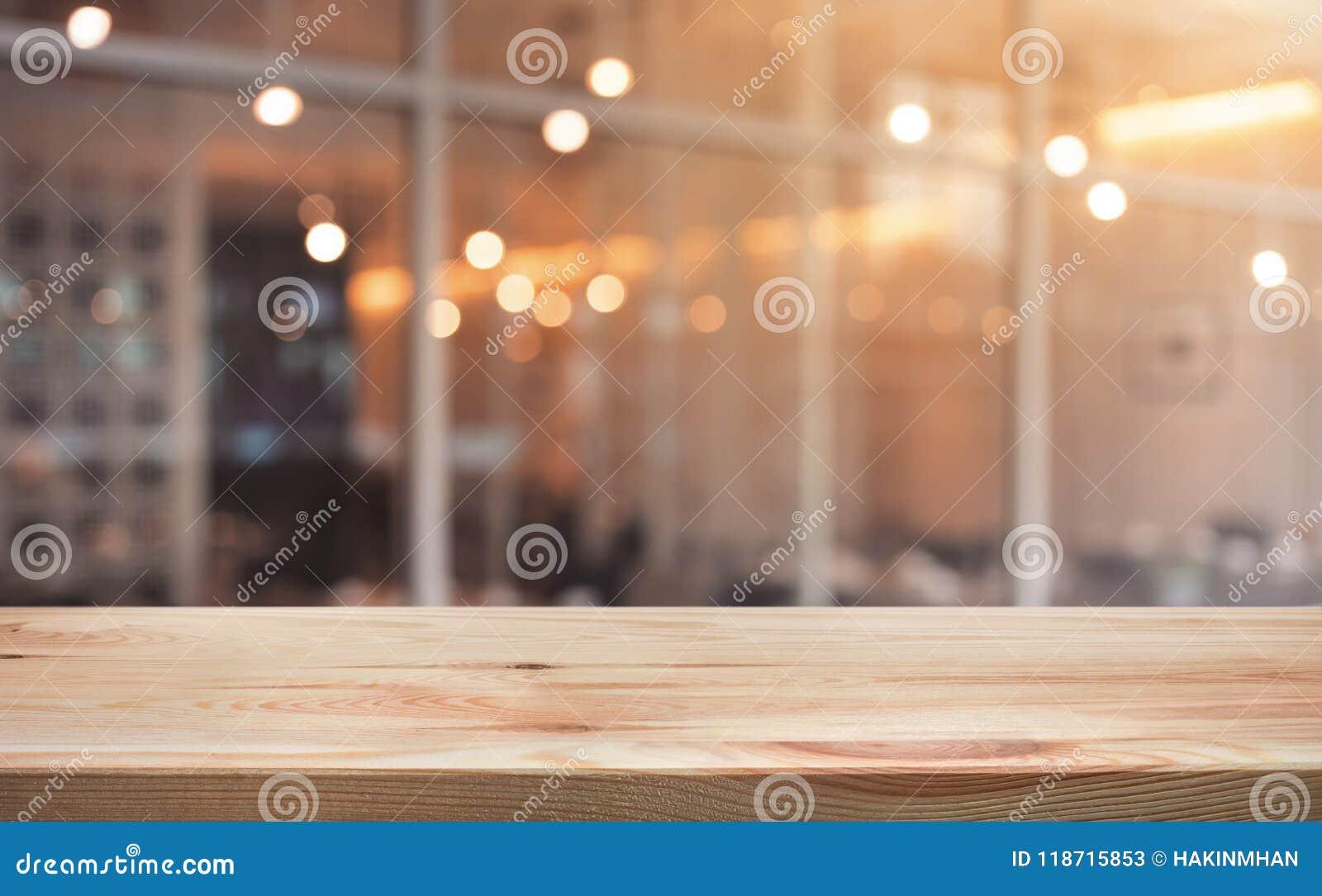 Hölzerne Tischplatte mit hellem Goldcafé, Restauranthintergrund