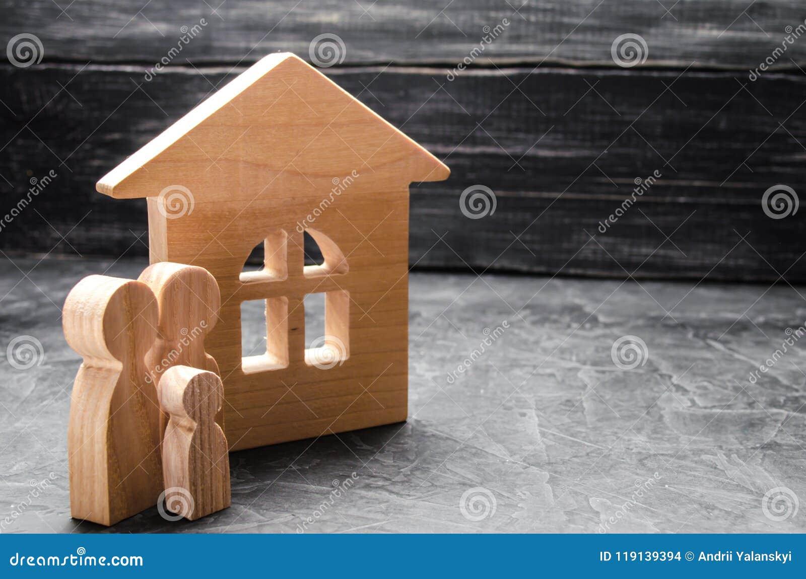 Hölzerne Zahlen der Familie stehen nahe einem Holzhaus Das Konzept des Findens eines neuen Hauses, bewegend Eine gesunde starke F