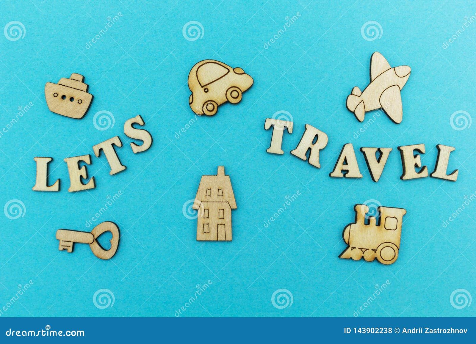 Hölzerne Zahlen eines Flugzeuges, ein Zug, ein Schiff, ein Auto Die Aufschrift 'ließ uns auf einen blauen Hintergrund reisen '