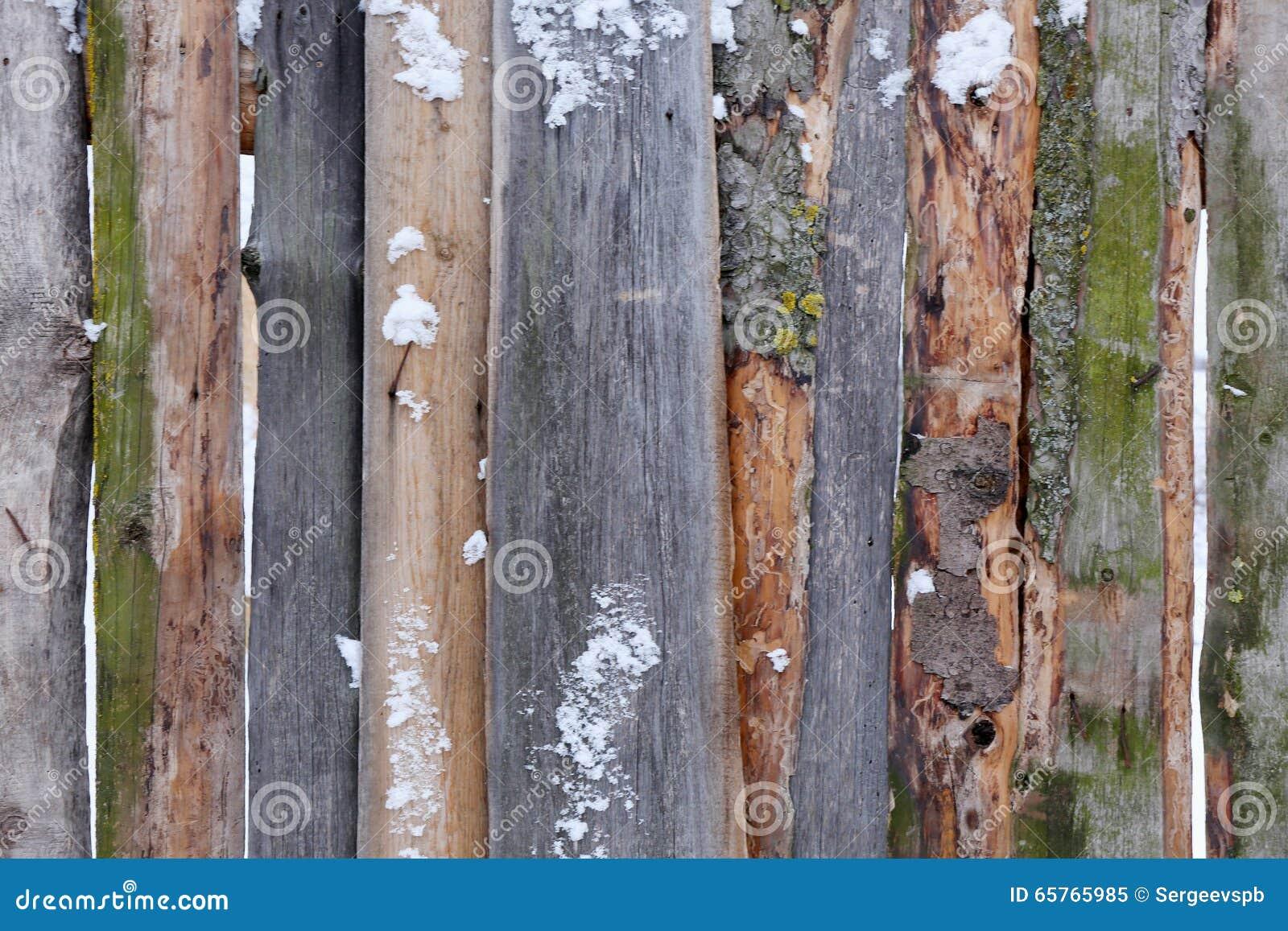 Hölzerner brauner Zaun von rauen Brettern im Schnee