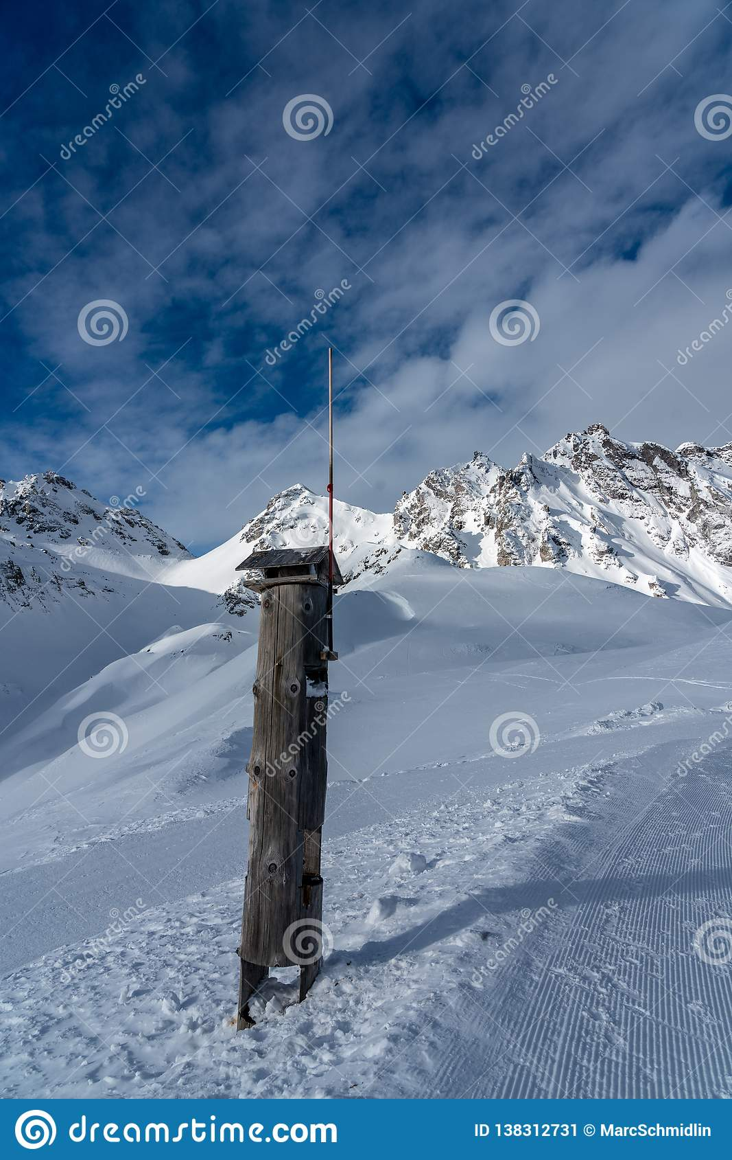 Hölzerner Fütterungsplatz für Vögel mit einem Blitzableiter in den hohen Alpen