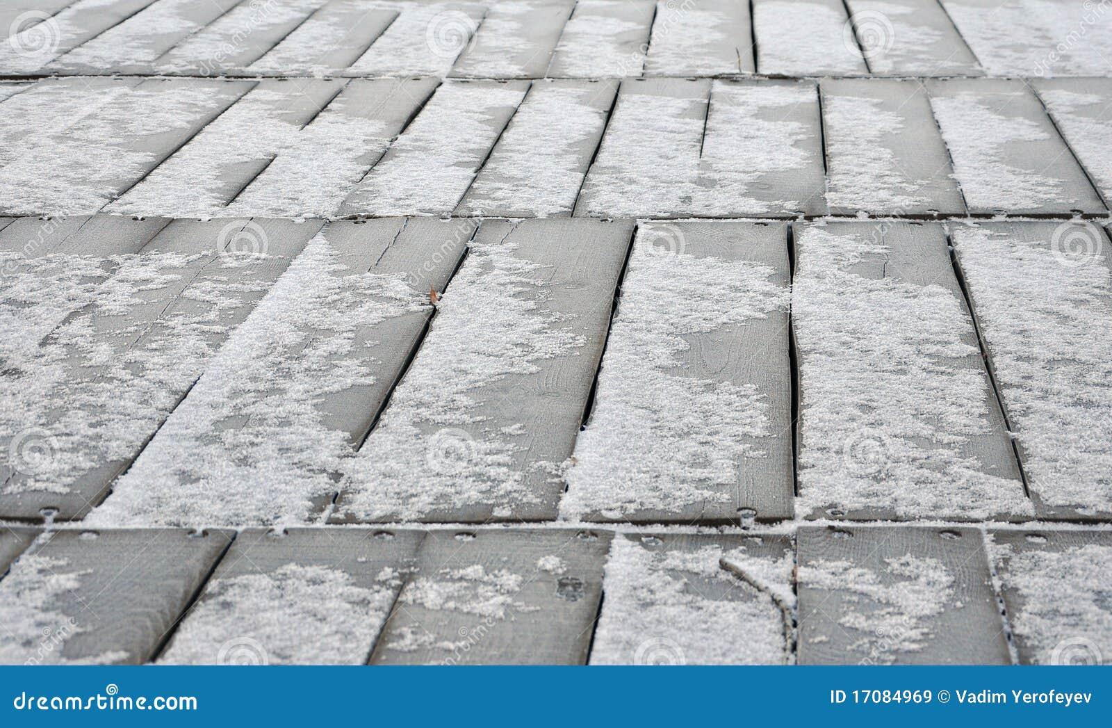 Hölzerner Fußboden deckte Schnee ab
