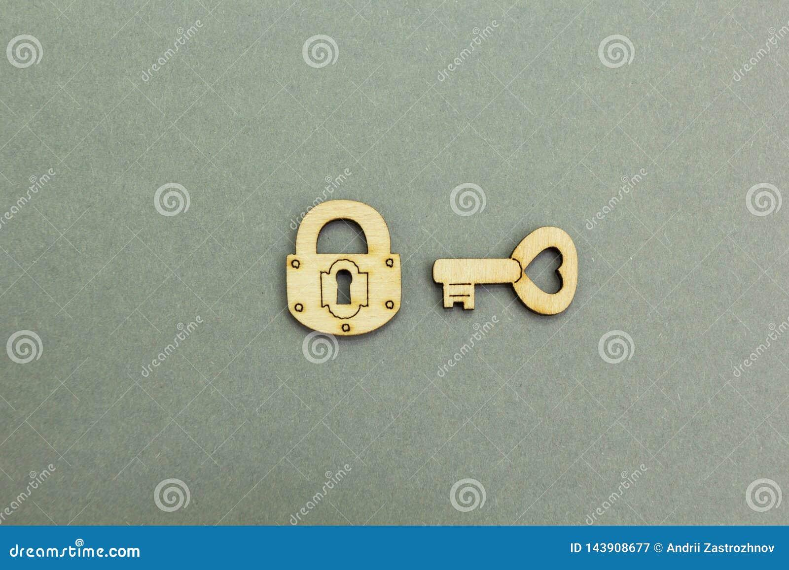 Hölzerner Verschluss und Schlüssel auf einem grauen Hintergrund