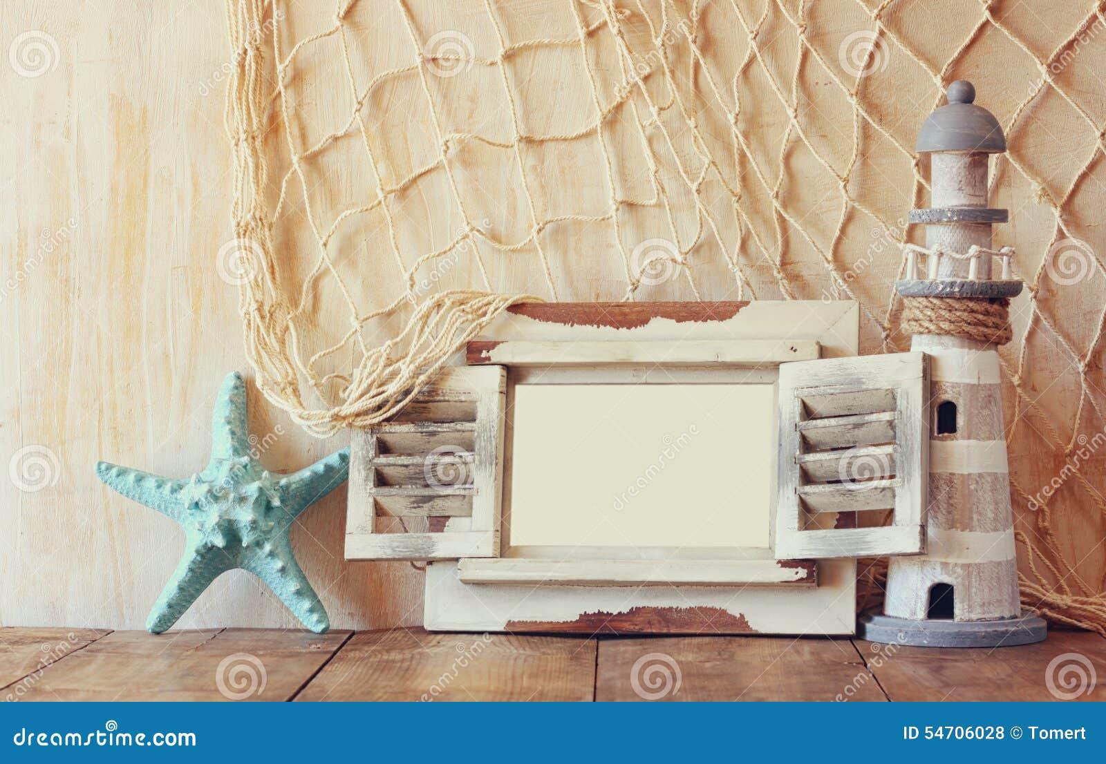 Hölzerner weißer Rahmen und Leuchtturm der alten Weinlese auf Holztisch Weinlese gefiltertes Bild Seelebensstilkonzept