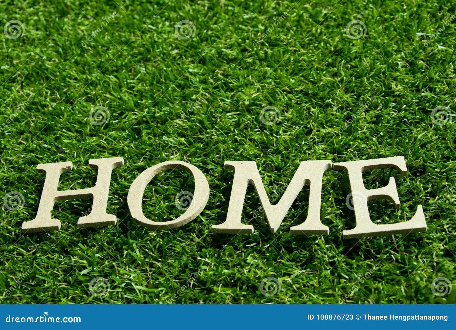 Hölzernes Alphabet im Benennungshaus auf künstlichem grünes Gras backgr